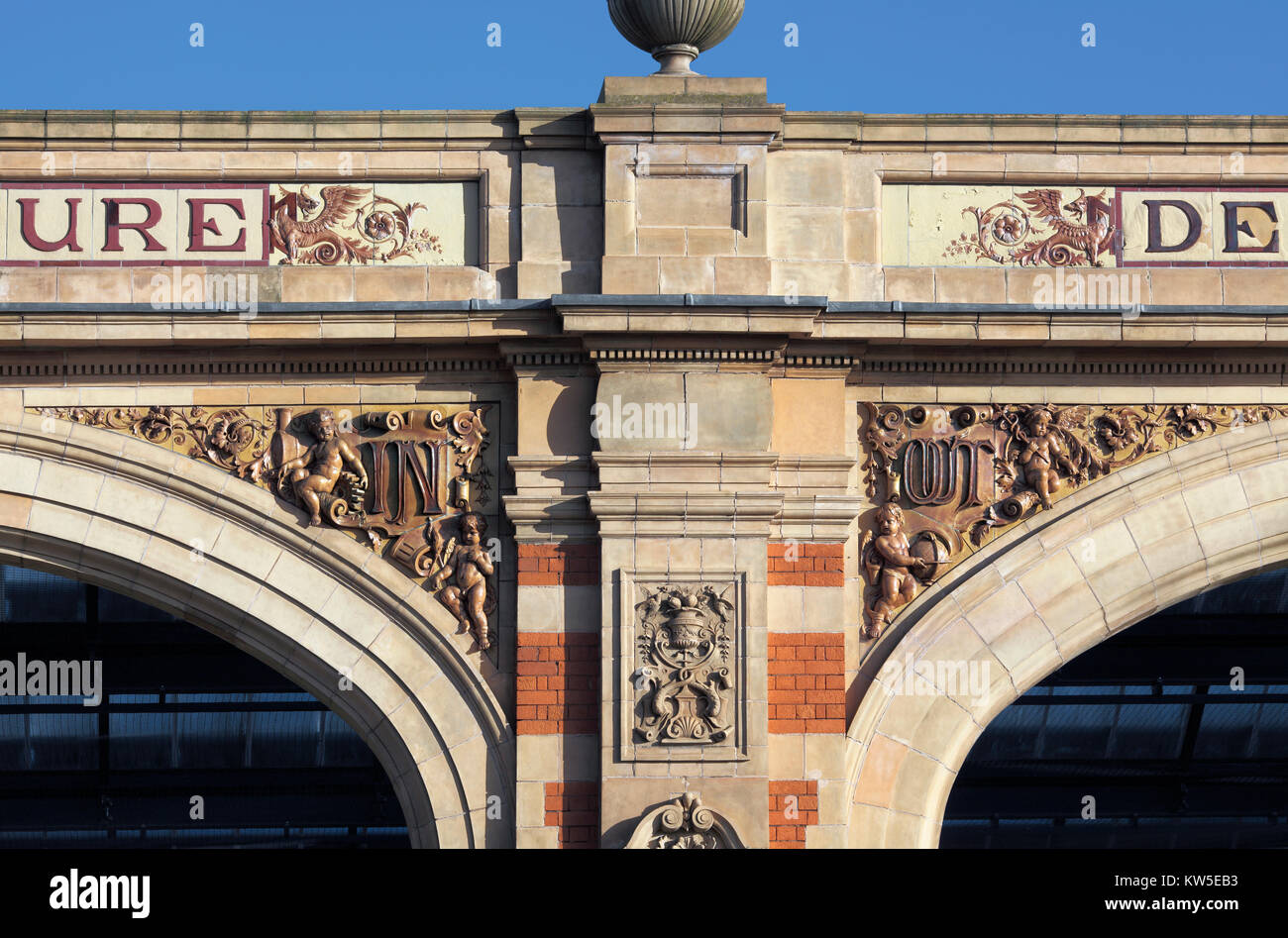 Ornate 'In' and 'Out' lettering in spandrels on the arched frontage of the late-Victorian (1892) - Stock Image