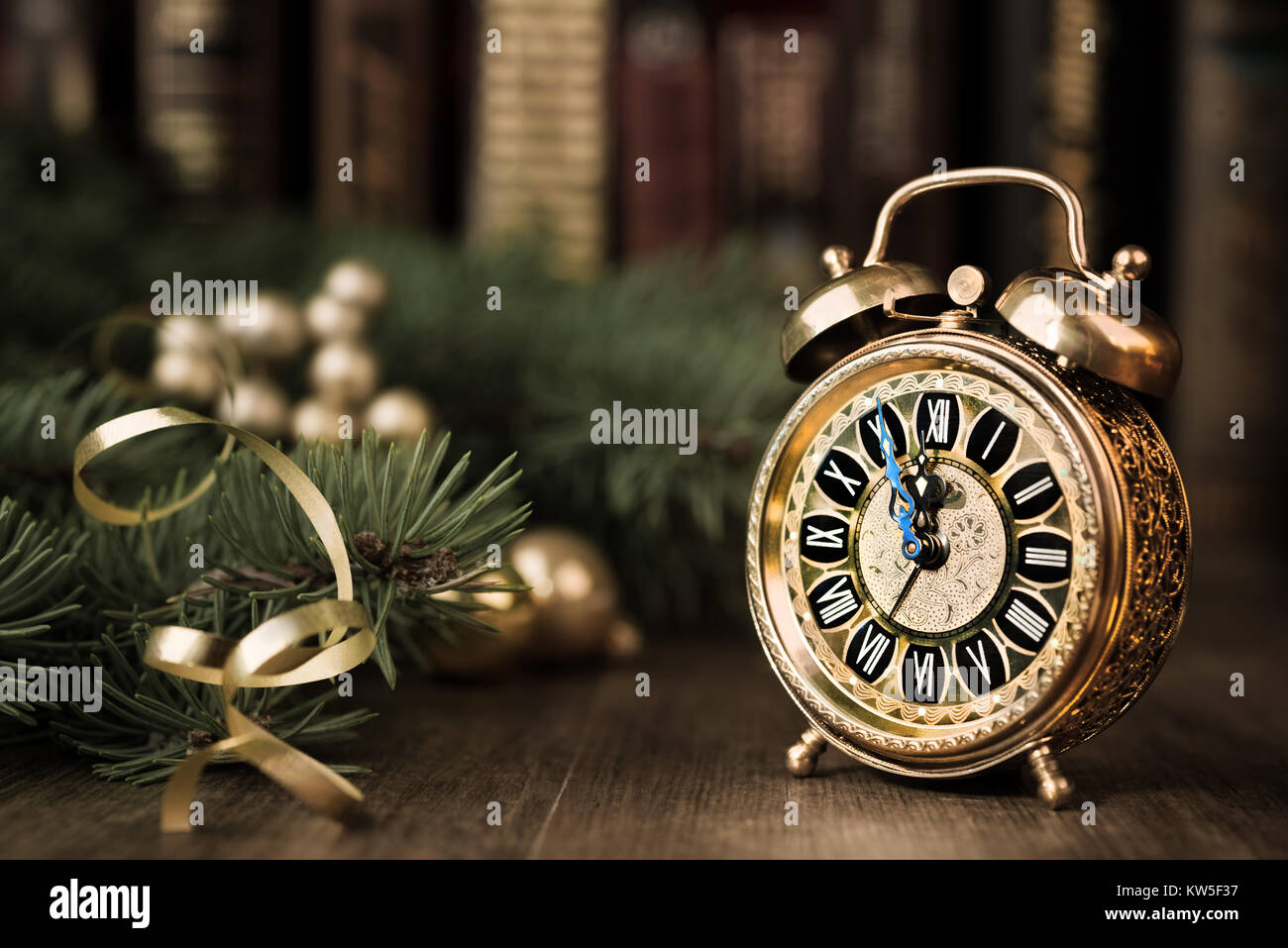 Vintage alarm clock in traditional study room showing five to midnight. Happy New Year! Stock Photo