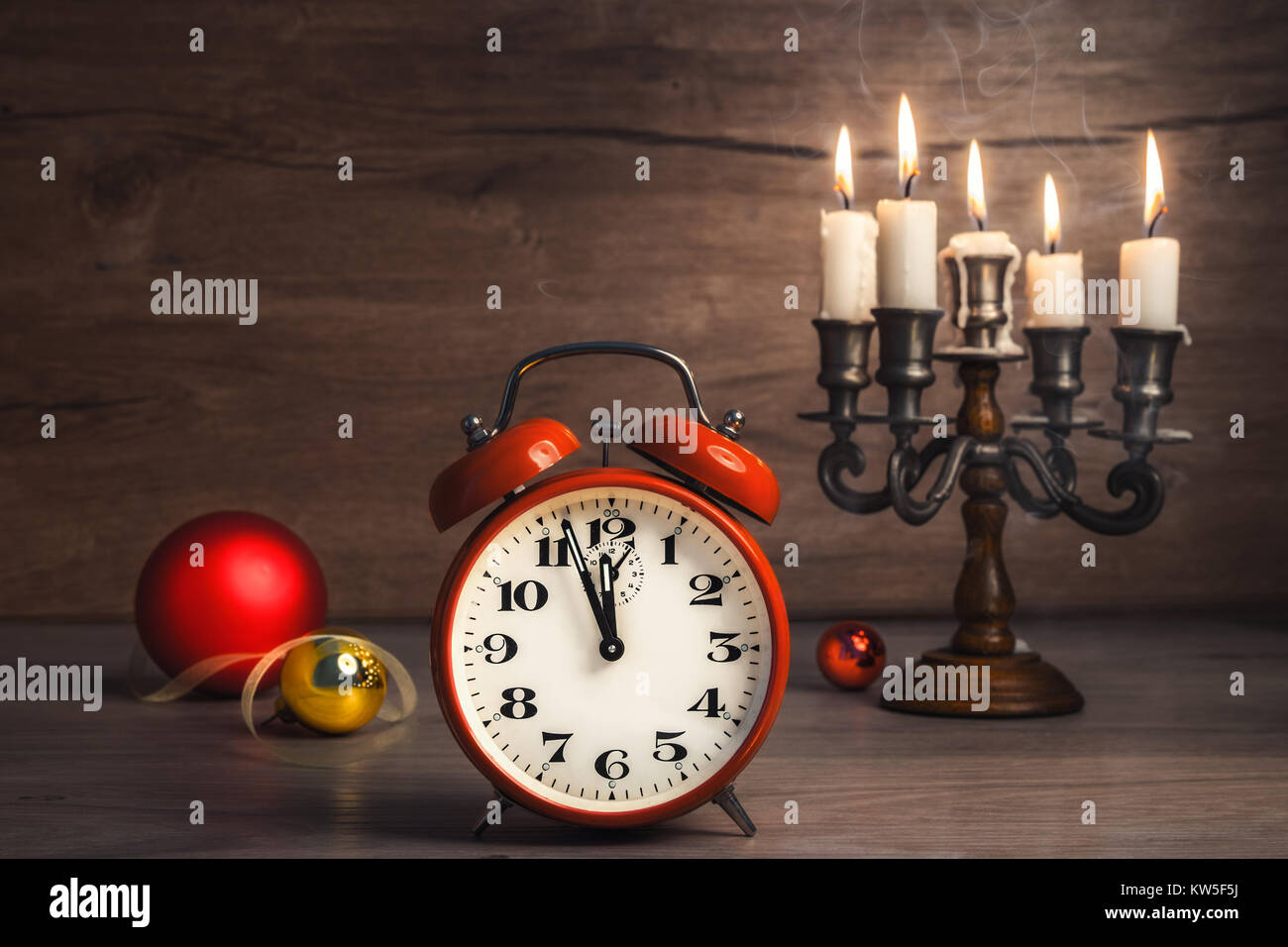 Vintage alarm clock showing five to twelve with Christmas baubles on wood. Happy New Year 2017! Stock Photo