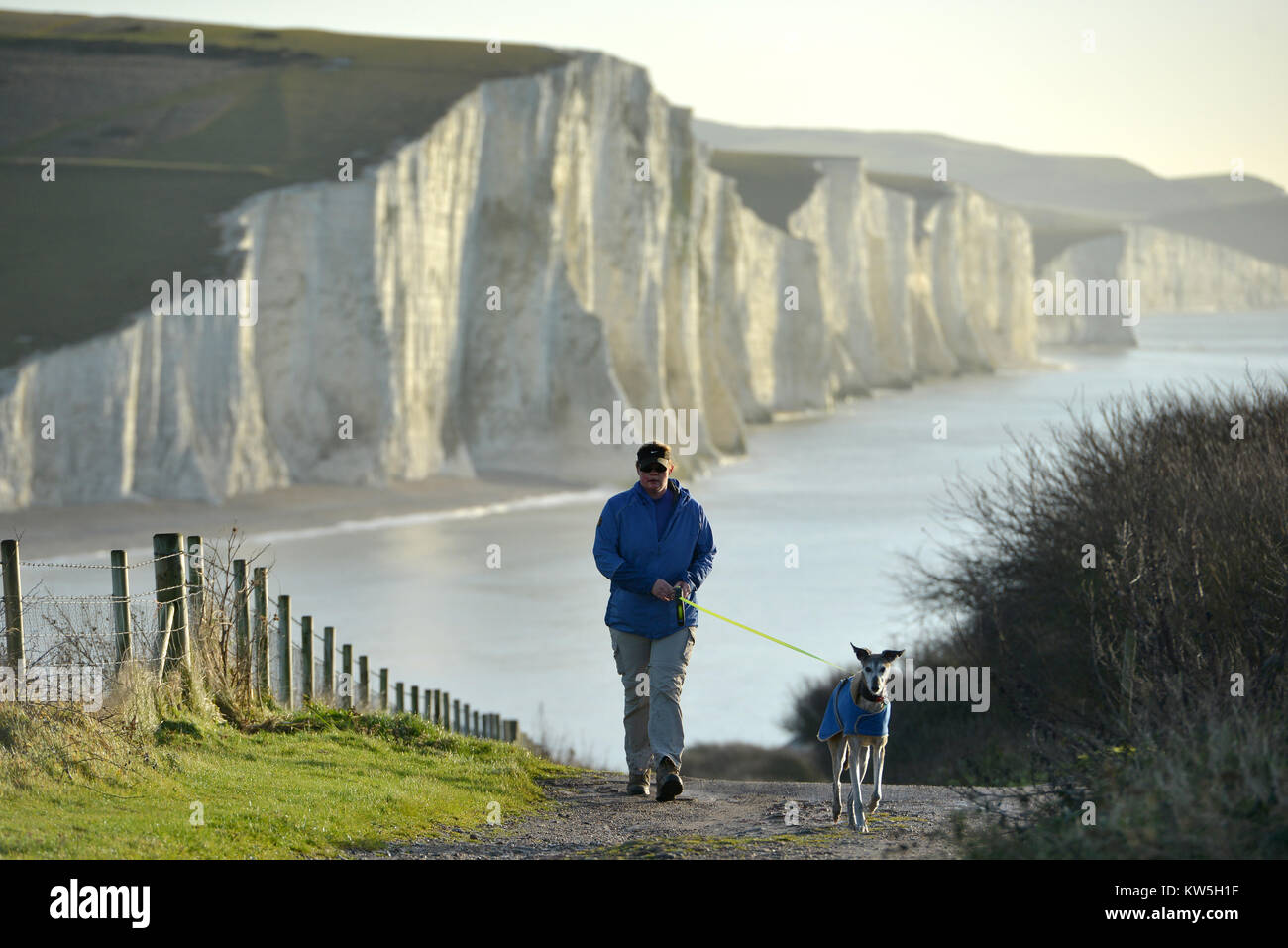 Person walking a dog on the South Downs, East Sussex, with the famous Seven Sisters chalk cliffs behind. Stock Photo