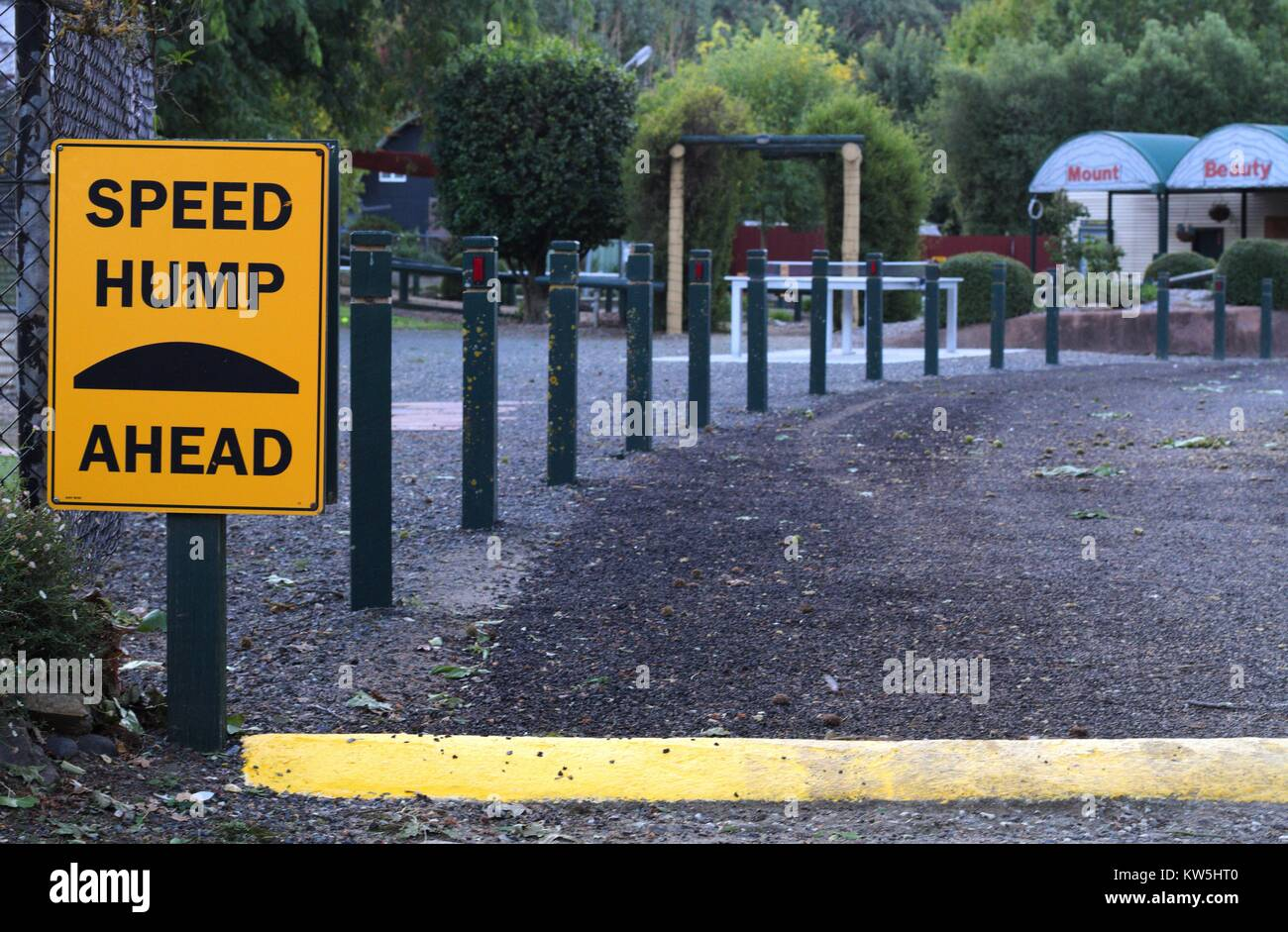 Speed hump sign beside a driveway with fence behind. Stock Photo