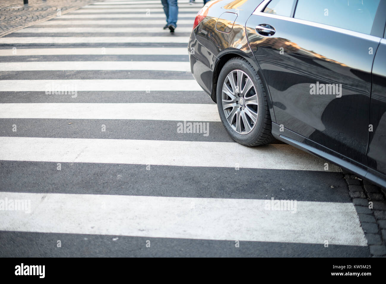A car partially parked across a zebra crossing - Stock Image