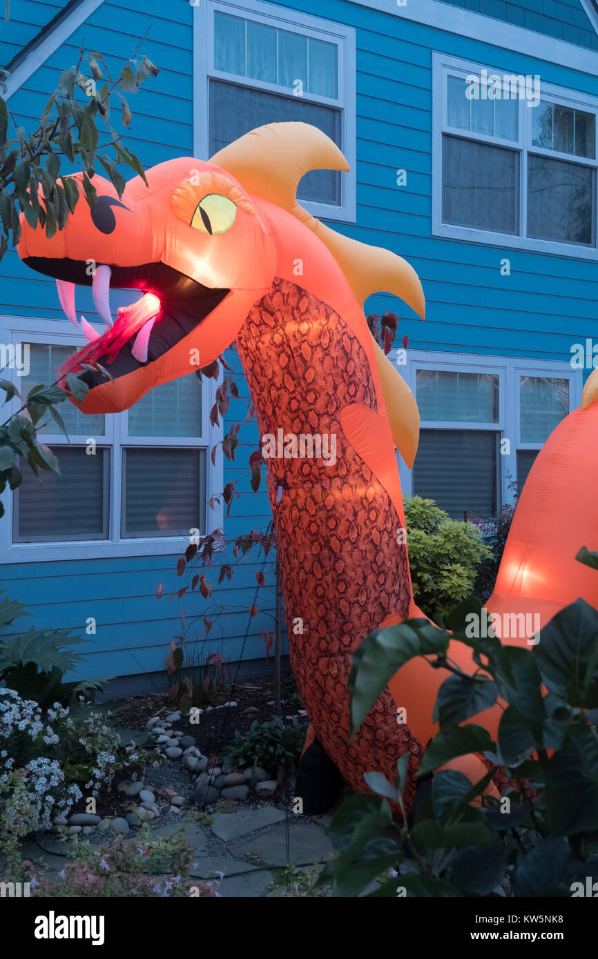 An inflatable fire breathing dragon in a front yard for Halloween. - Stock Image