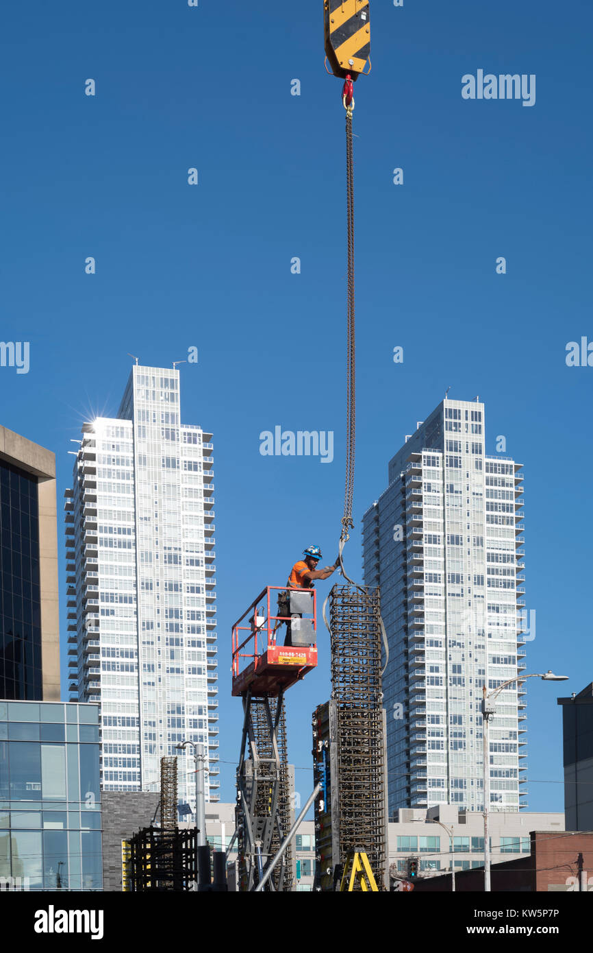 Laborer guiding  a form being lifted by a crane, Belltown, Seattle, Washington, USA - Stock Image