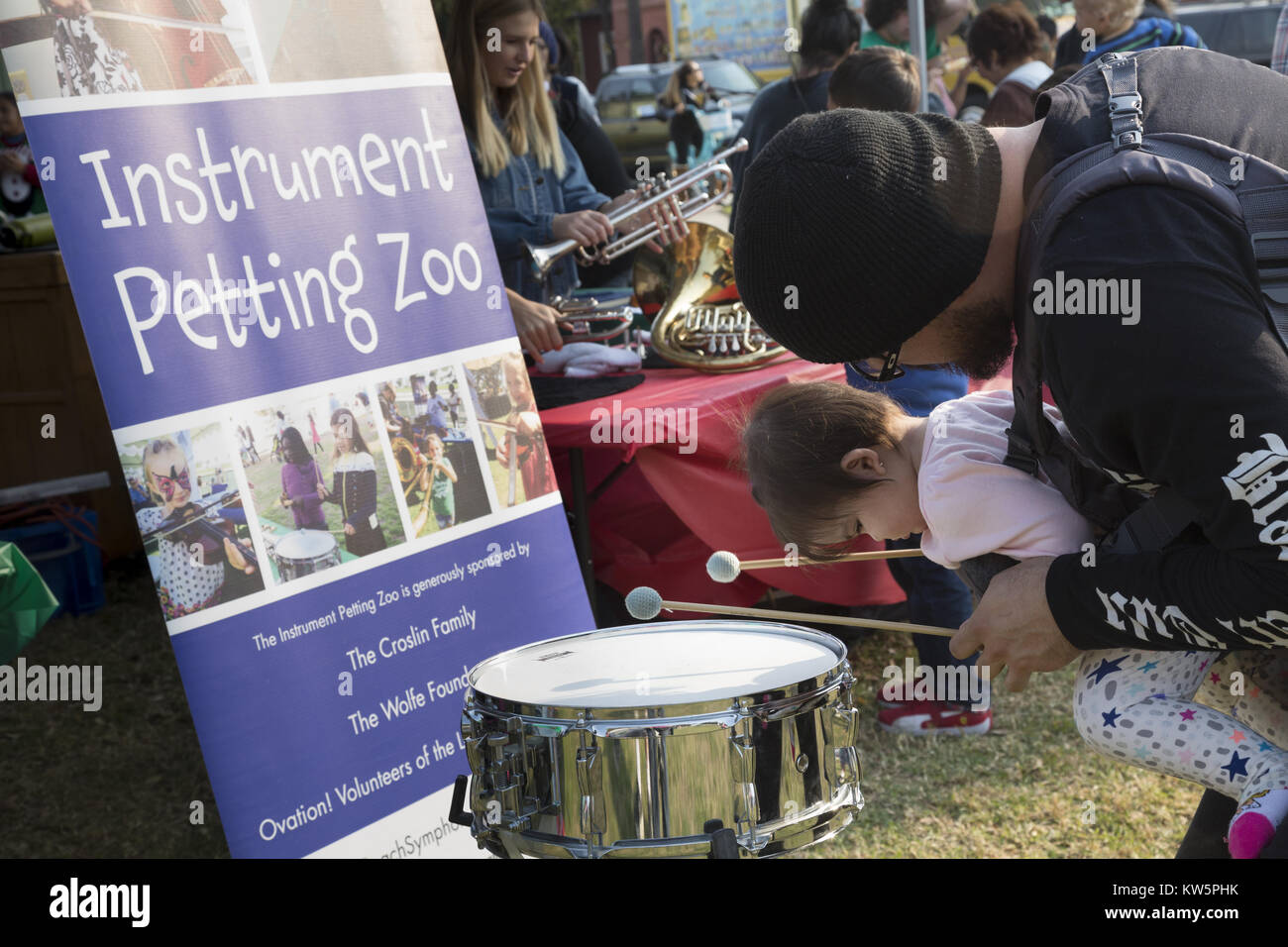 A father leans over to drum with his toddler daughter in a chest carrier at Long Beach Symphoy's Instrument - Stock Image