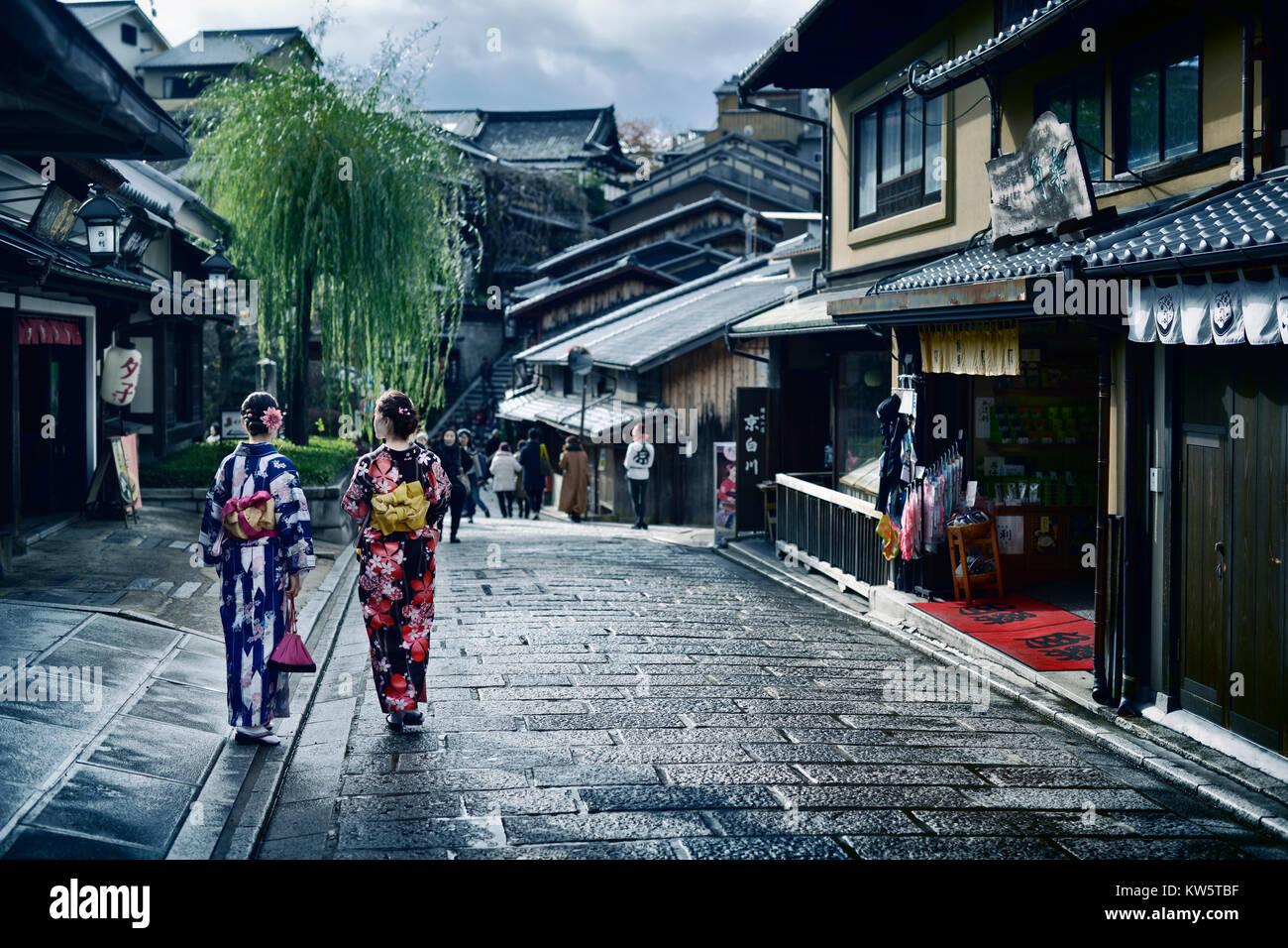 Two girls in bright Yukata kimonos with their obi tied in a bow walking down Yasaka dori street in Kyoto near Kiyomizu - Stock Image
