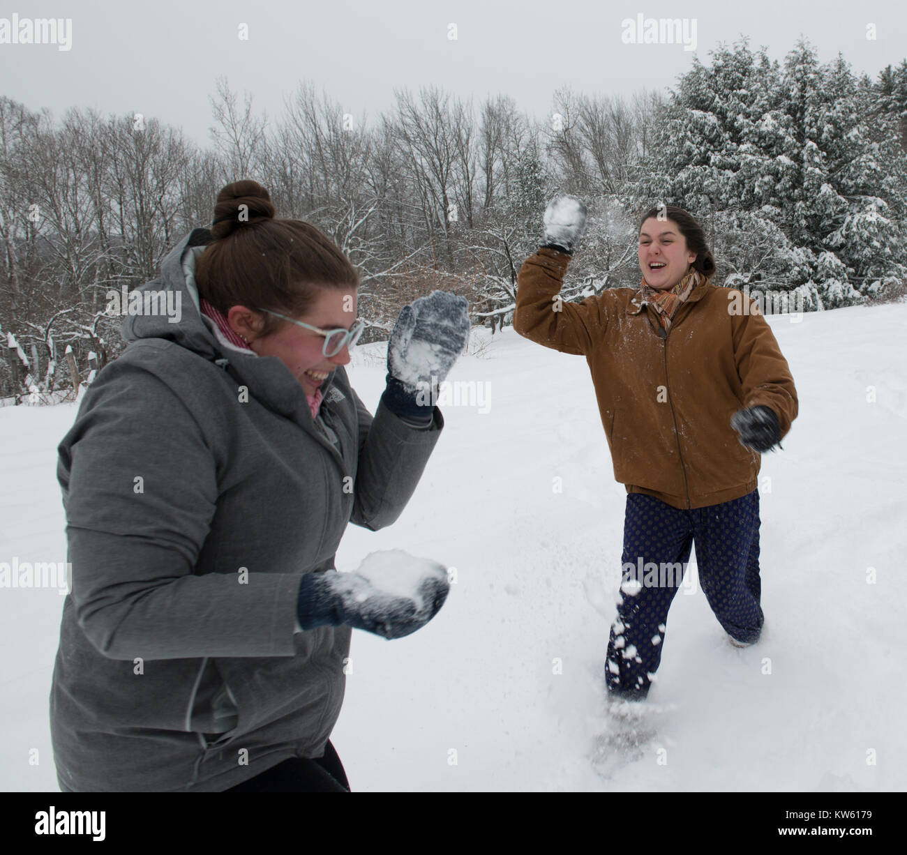 Sisters Eliza, 26, left and Georgia Doolittle, 17 have a snow ball fight in Maine - Stock Image