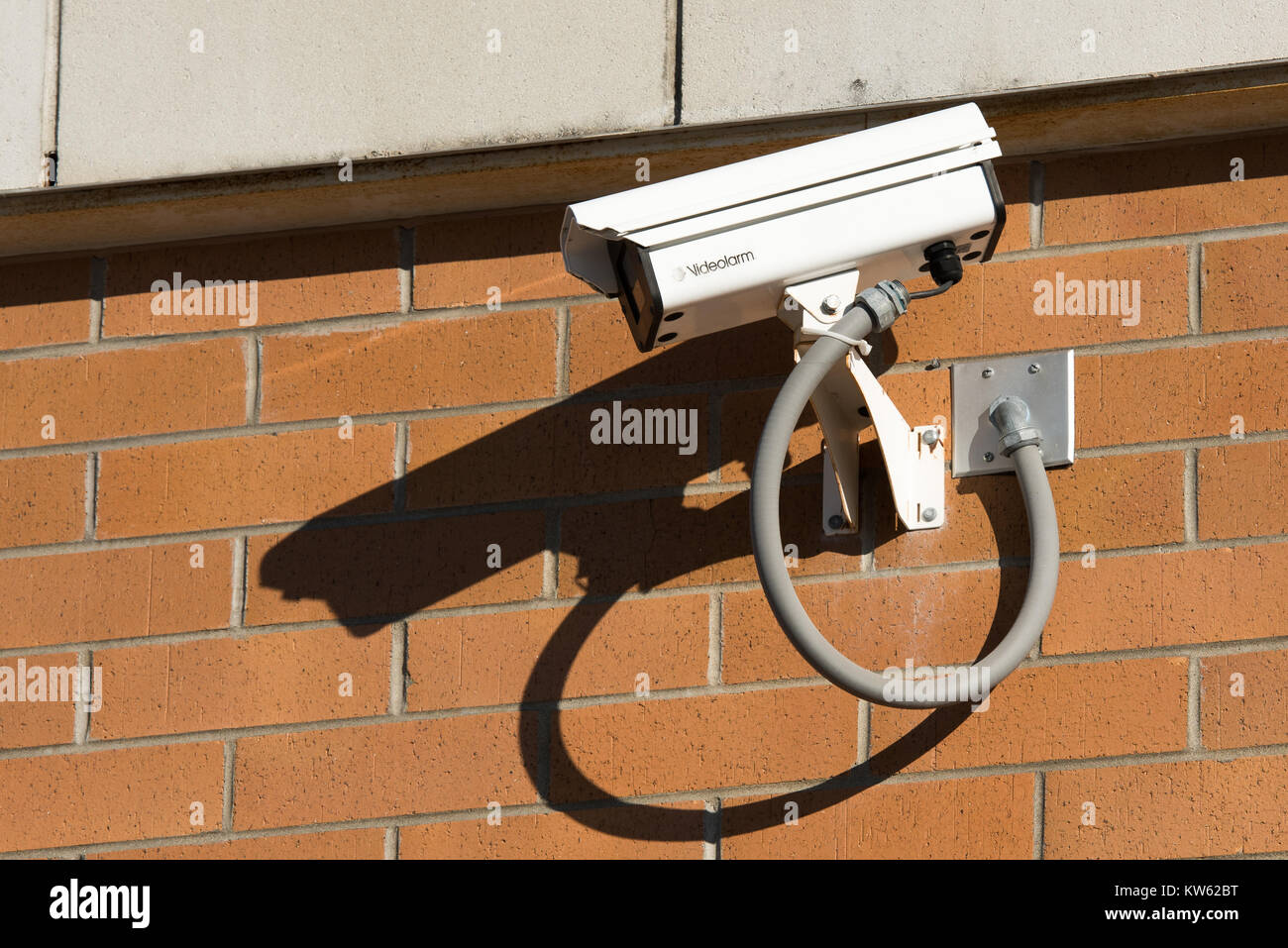A surveillance camera on a brick wall of a store in Gloversville, NY USA Stock Photo