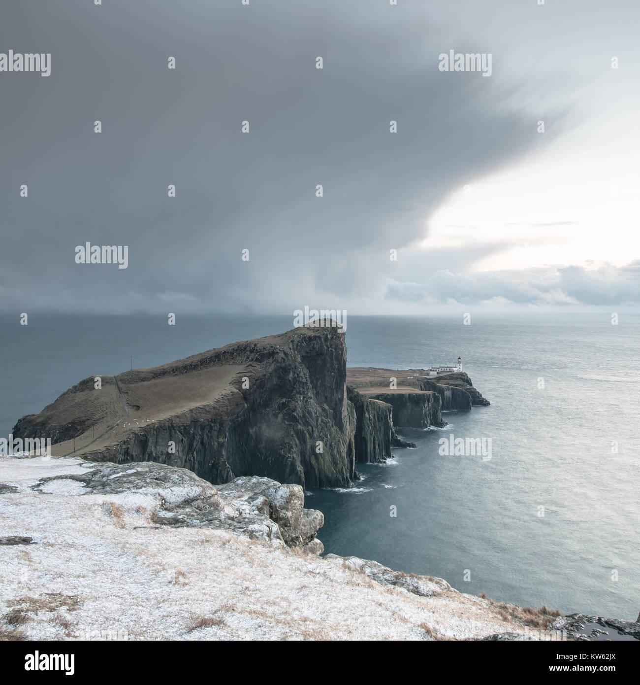 Neist Point Peninsula with White Lighthouse - Isle of Skye Landscape with Stormy Clouds on Sky, Dramatic Cliffs Stock Photo
