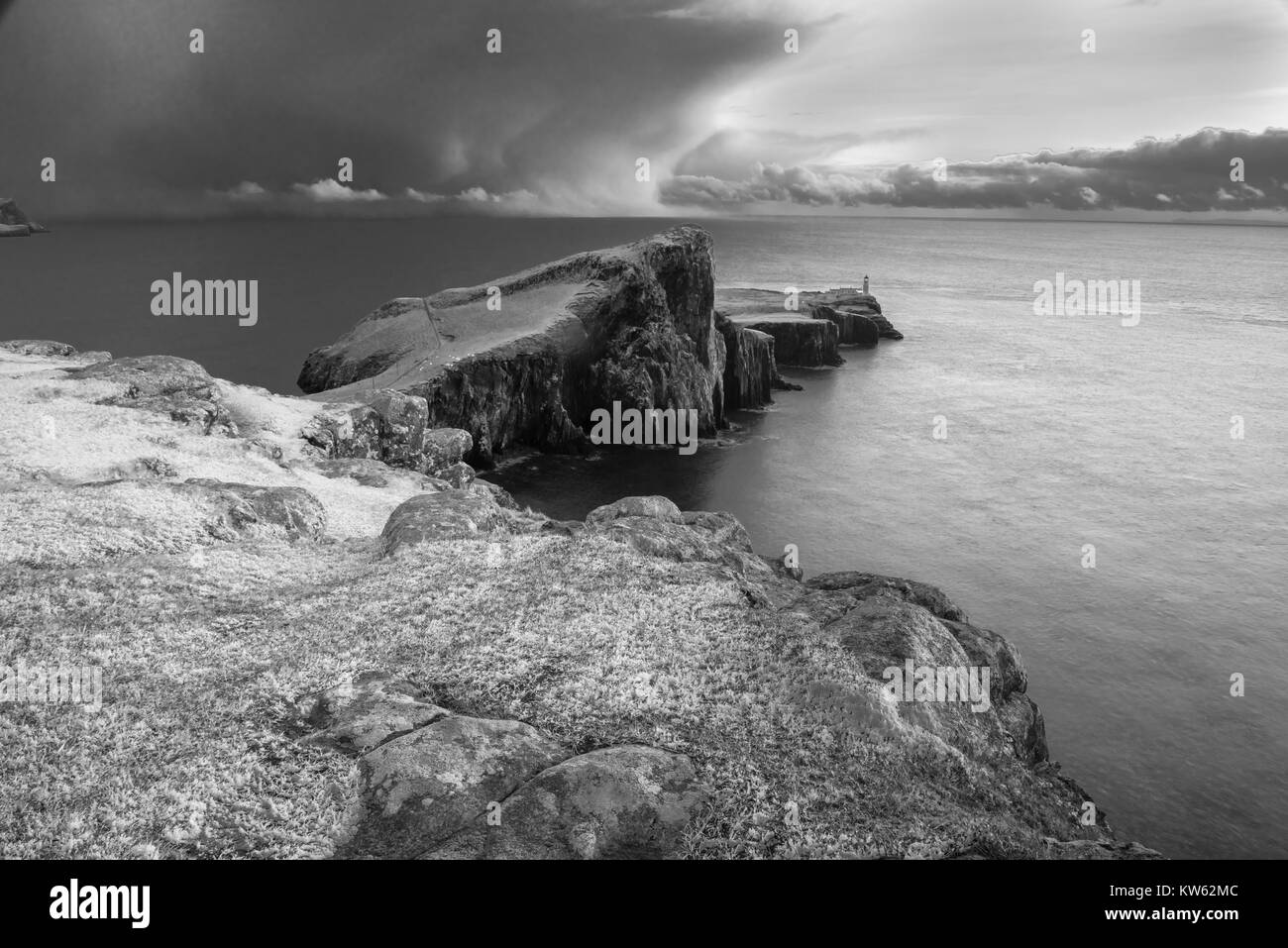 Neist Point Peninsula with White Lighthouse - Isle of Skye Landscape with Stormy Clouds on Sky, Dramatic Cliffs - Stock Image