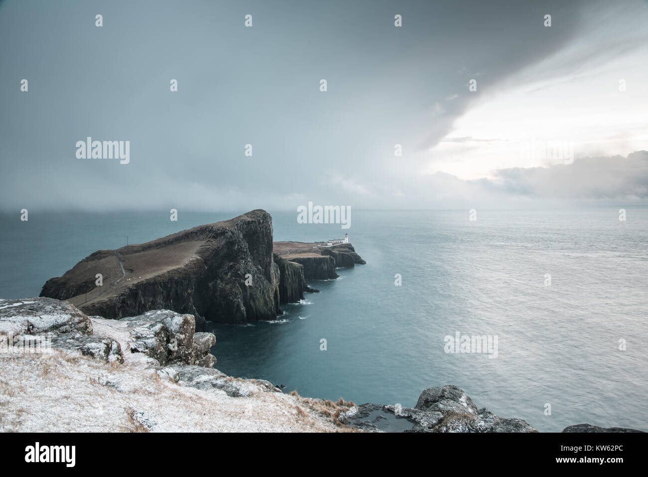 Neist Point Peninsula with White Lighthouse - Isle of Skye Landscape with Stormy Clouds on Sky, Dramatic Cliffs and Spectacular Scottish Scenery Stock Photo