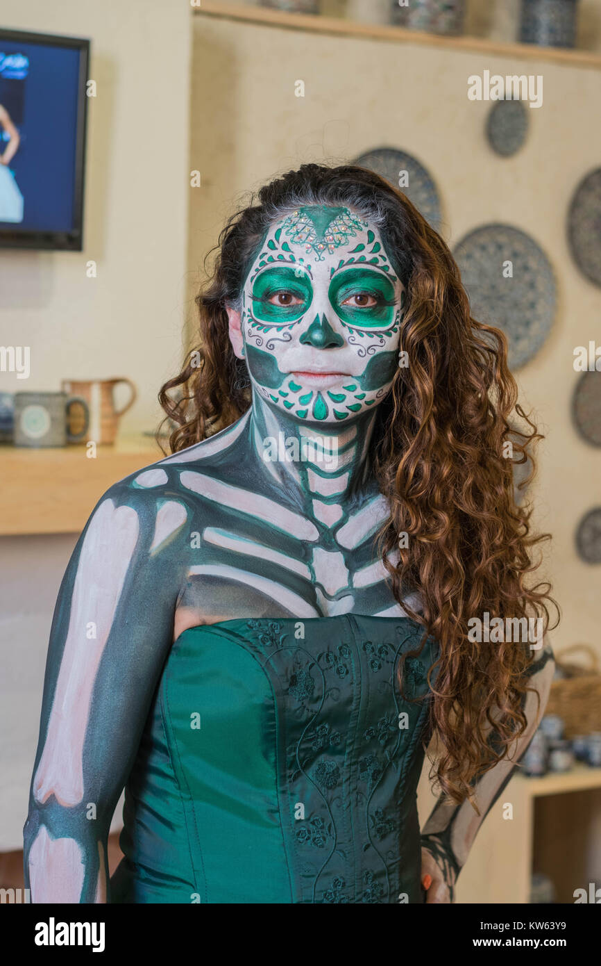 Young woman with long brown curly hair dressed in a green gown, face and body painted for the day of the dead celebration, - Stock Image