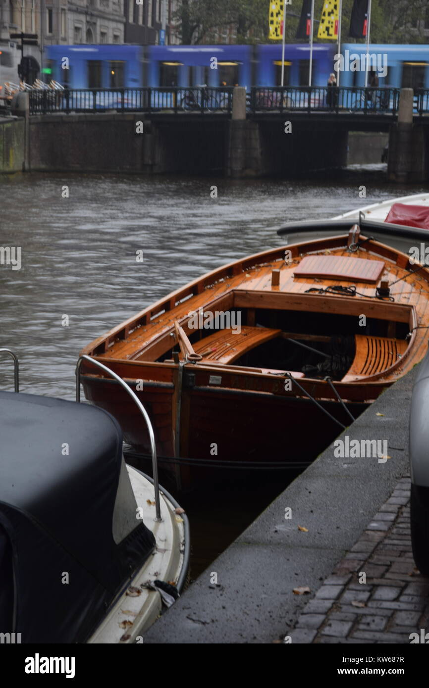 A boat floating on a channel in Amsterdam - Stock Image