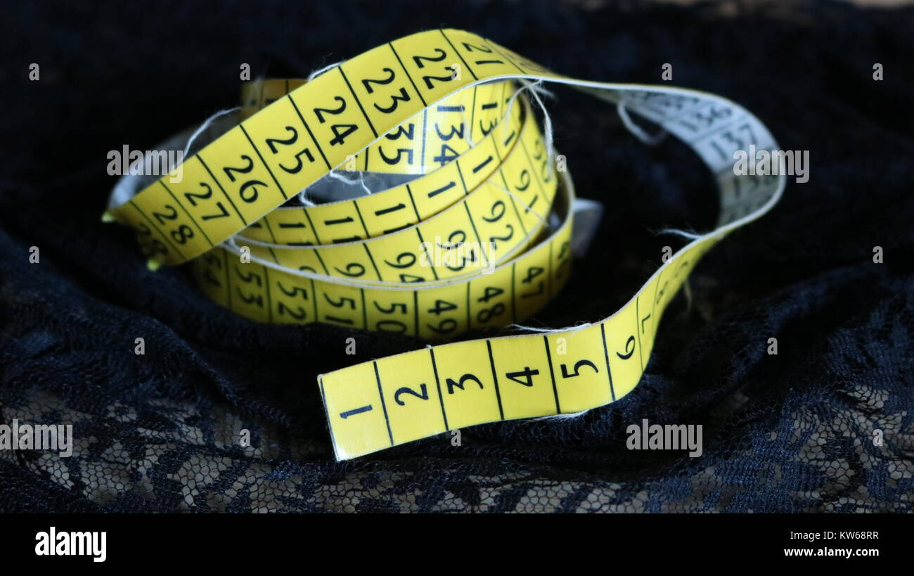 Yellow tailor measuring tape meter on black background - Stock Image