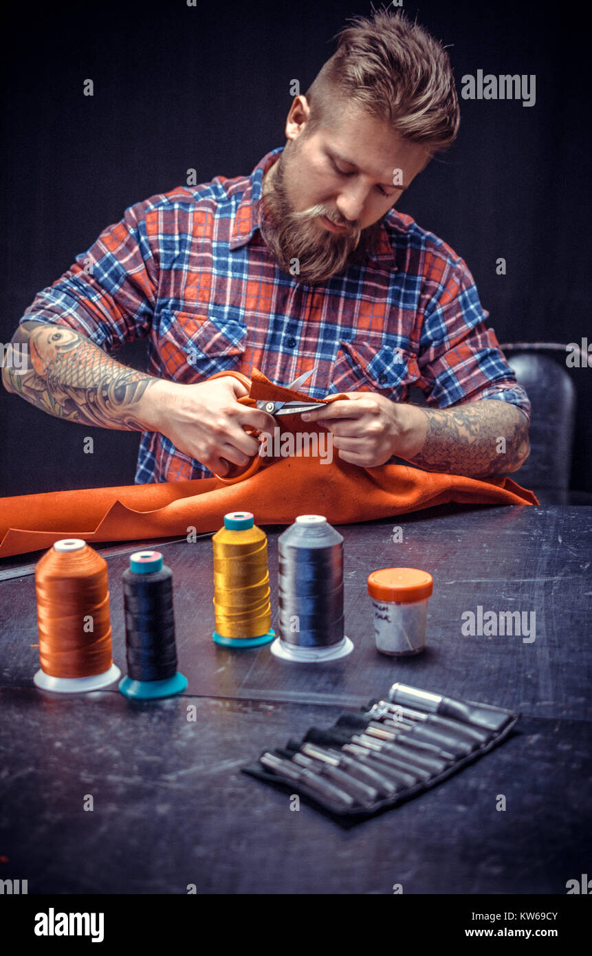 Worker of leather creates a new leatherwork at the tanning shop - Stock Image
