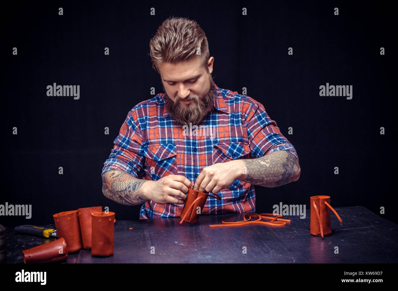 Leather workman creates quality product of leather in his shop - Stock Image