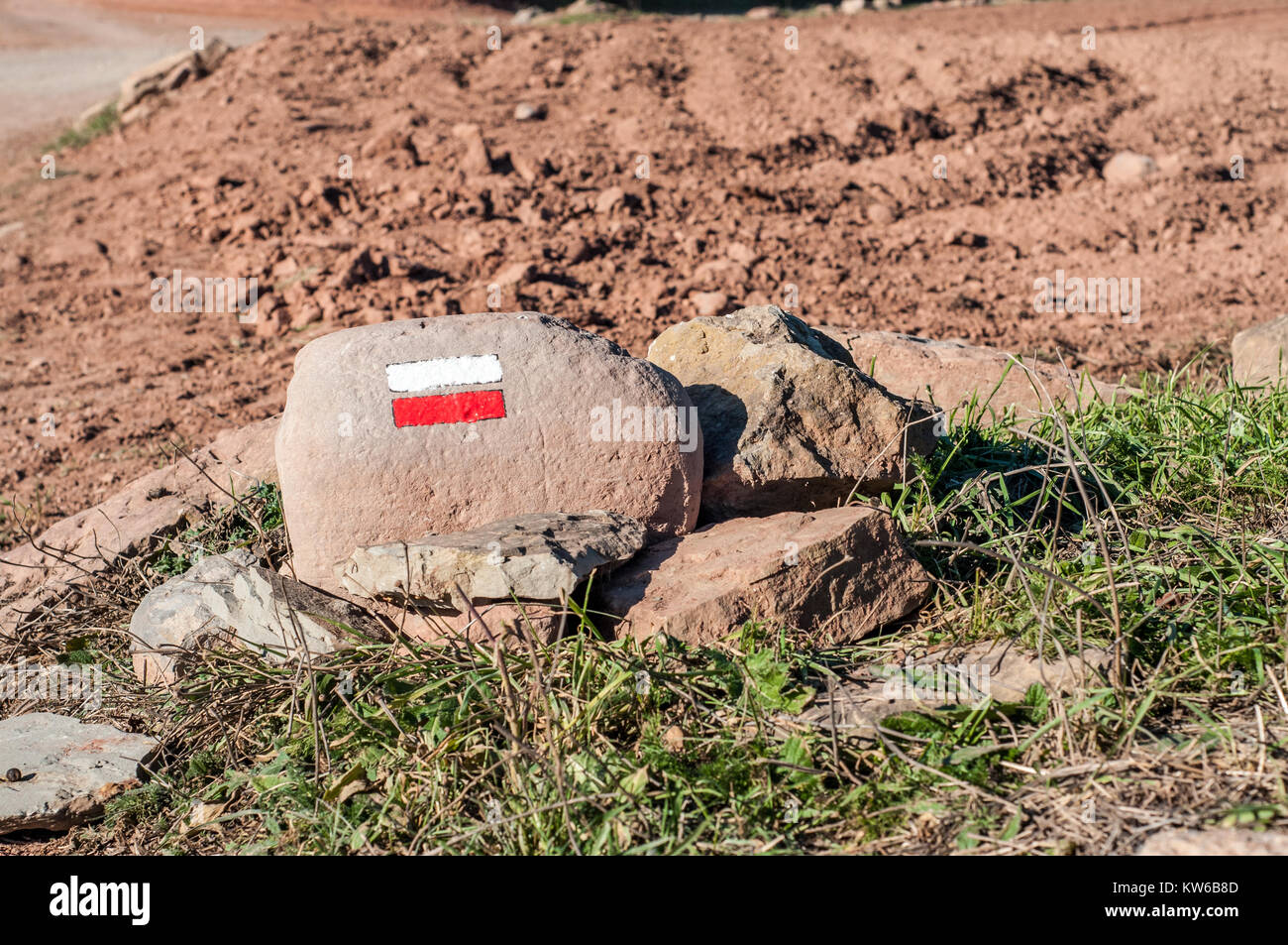 Stone landmark, sign with two horizontal lines, red and white to indicate the correct path, Santpedor, Catalonia, - Stock Image