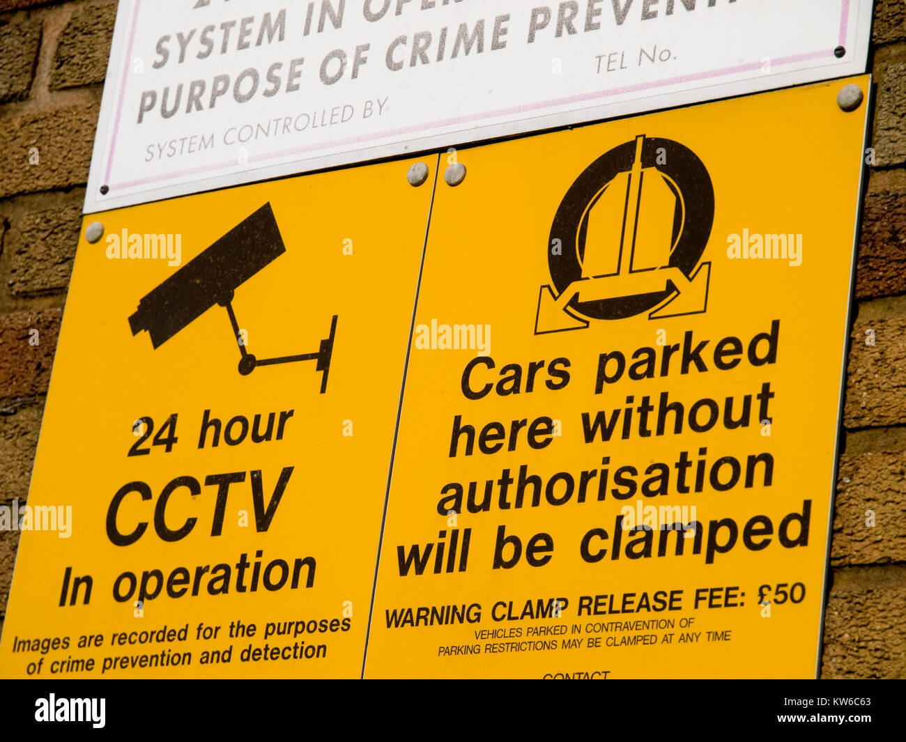 Security sign on a wall warning of clamping if parking is unauthorised - Stock Image