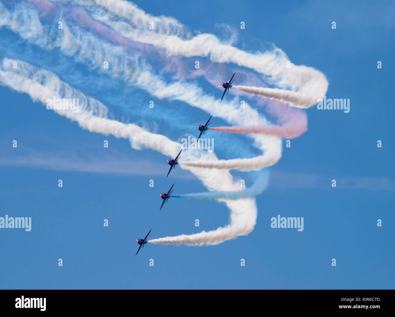 Five of the world famous Royal Air Force Red Arrows aeronautical display team carrying out a tight turn with vapour - Stock Image