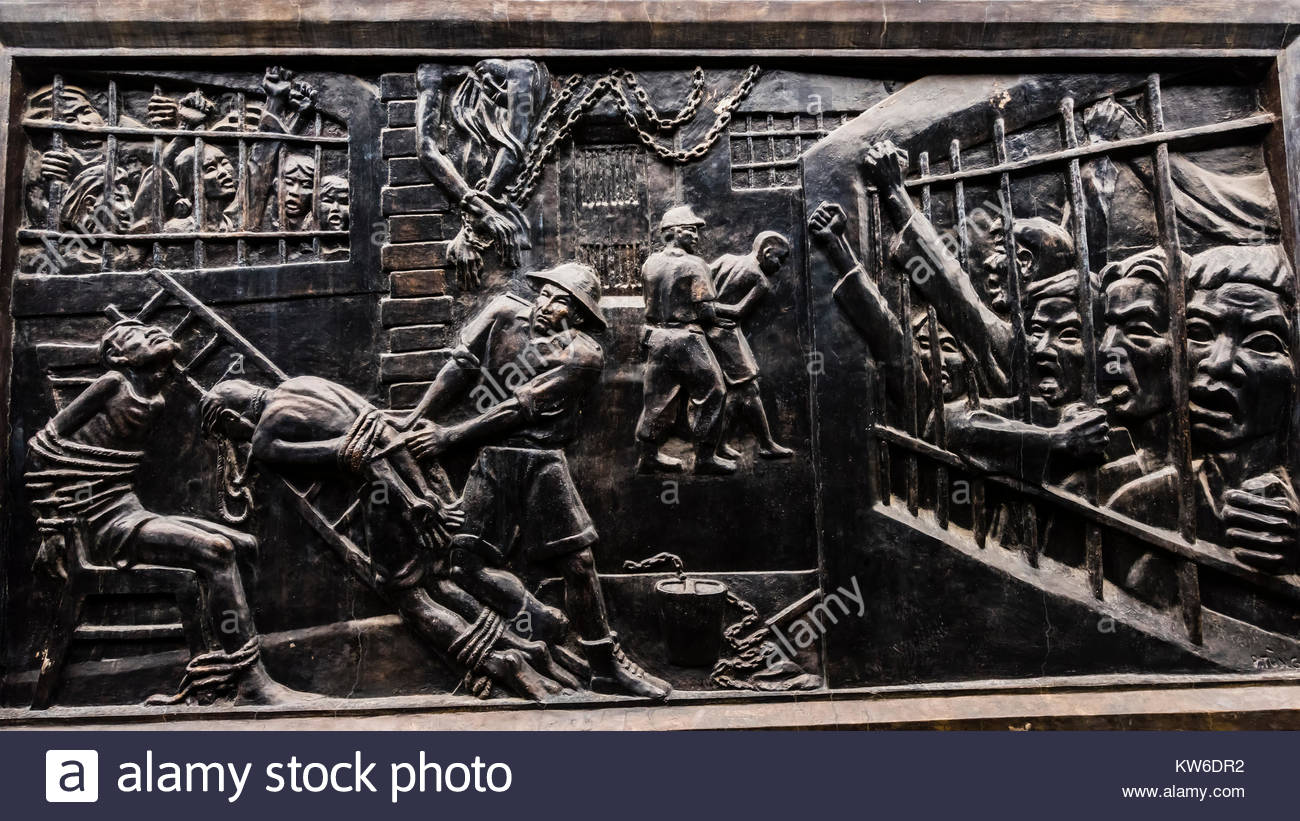 A bronze bas-relief showing inhumane treatment by the French (of Vietnamese prisoners) who had built the prison - Stock Image