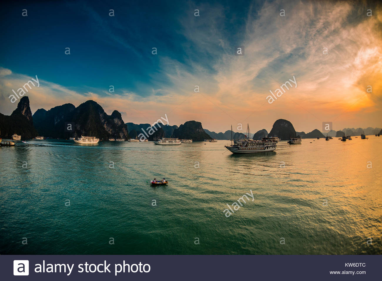 Sunset in Halong Bay, North Vietnam. The bay features 3,000  limestone and dolomite karsts and islets in various Stock Photo