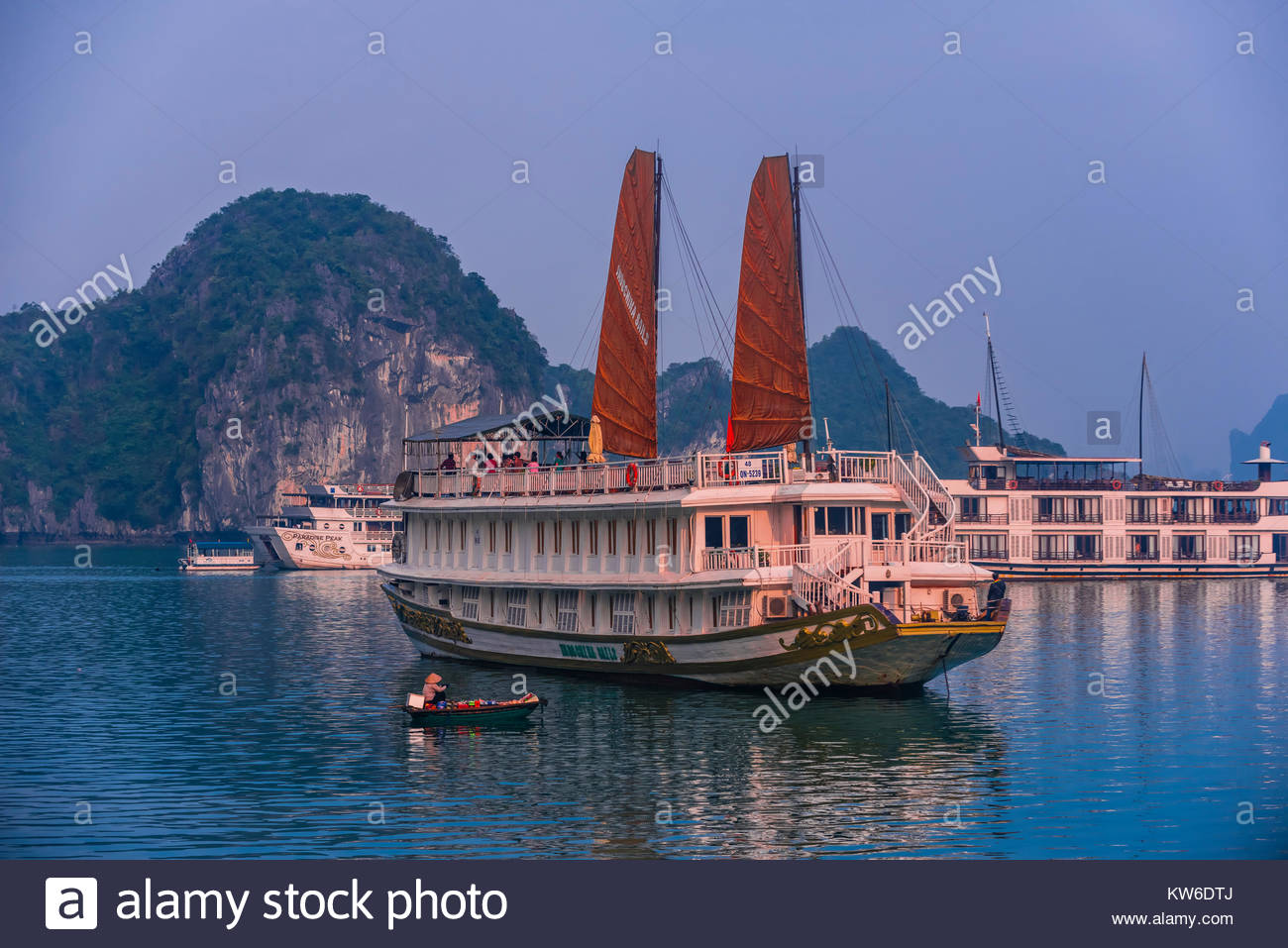 Tour ships with their junk sails up, Halong Bay, North Vietnam. The bay features 3,000  limestone and dolomite karsts - Stock Image