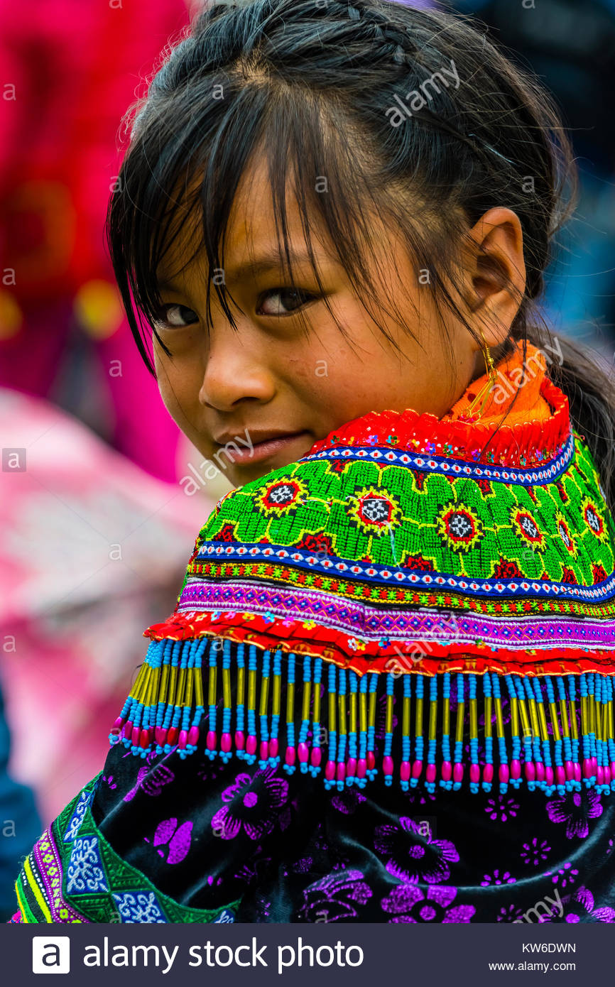 Flower Hmong (hill tribe) girl at the Sunday market at Ba Ha, northern Vietnam. Every Sunday ethnic minorities gather - Stock Image