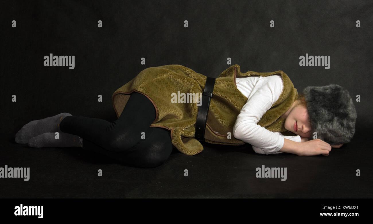 Young shepherd lying on the groung, sleeping - Stock Image