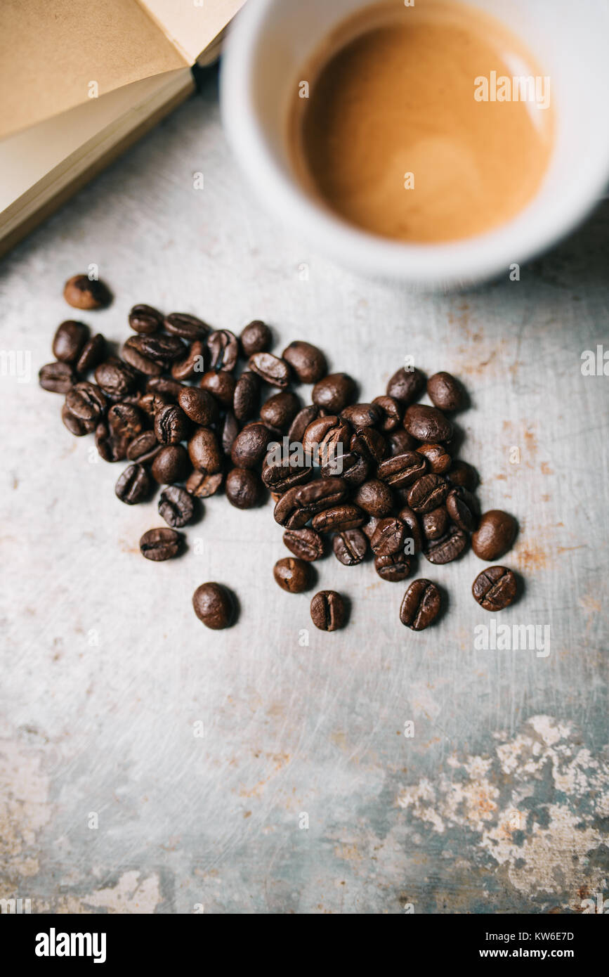 Fresh coffee beans and espresso on old metal surface - Stock Image