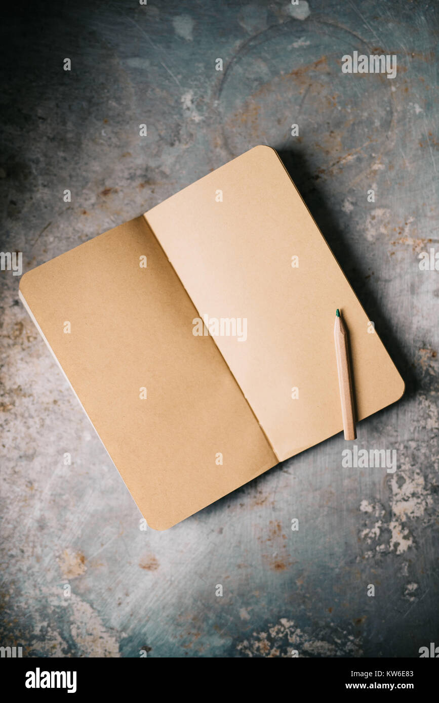 Little brown notepad on metal surface - Stock Image