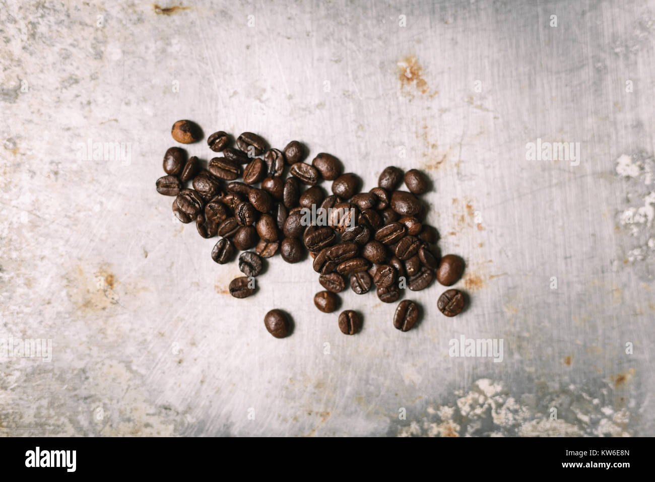 Roasted coffee bean on vintage metal surface - Stock Image