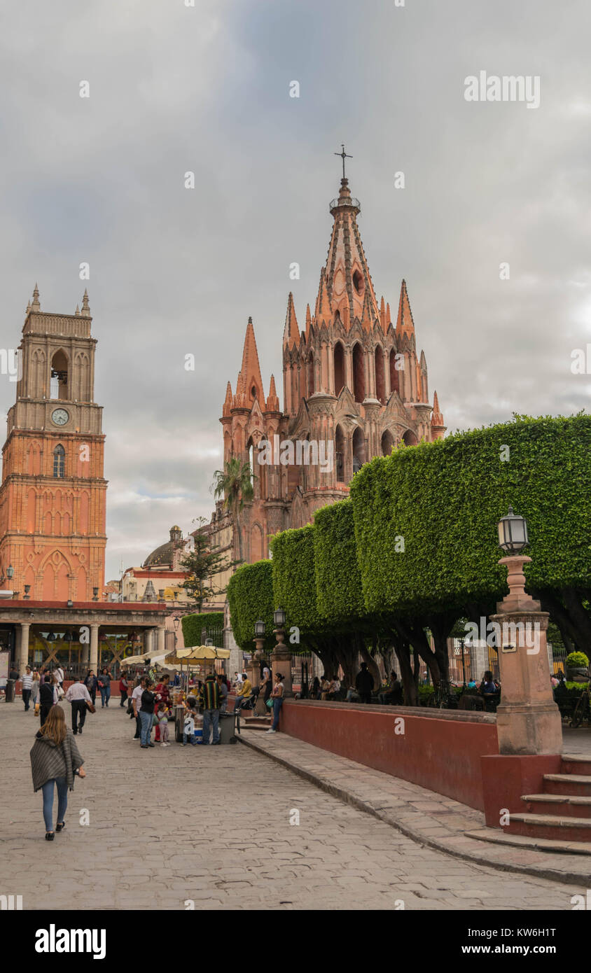 The beautiful pink Gothic Parroquia de San Miguel Arcangel towering above the El Jardin, with tourists and vendors, Stock Photo