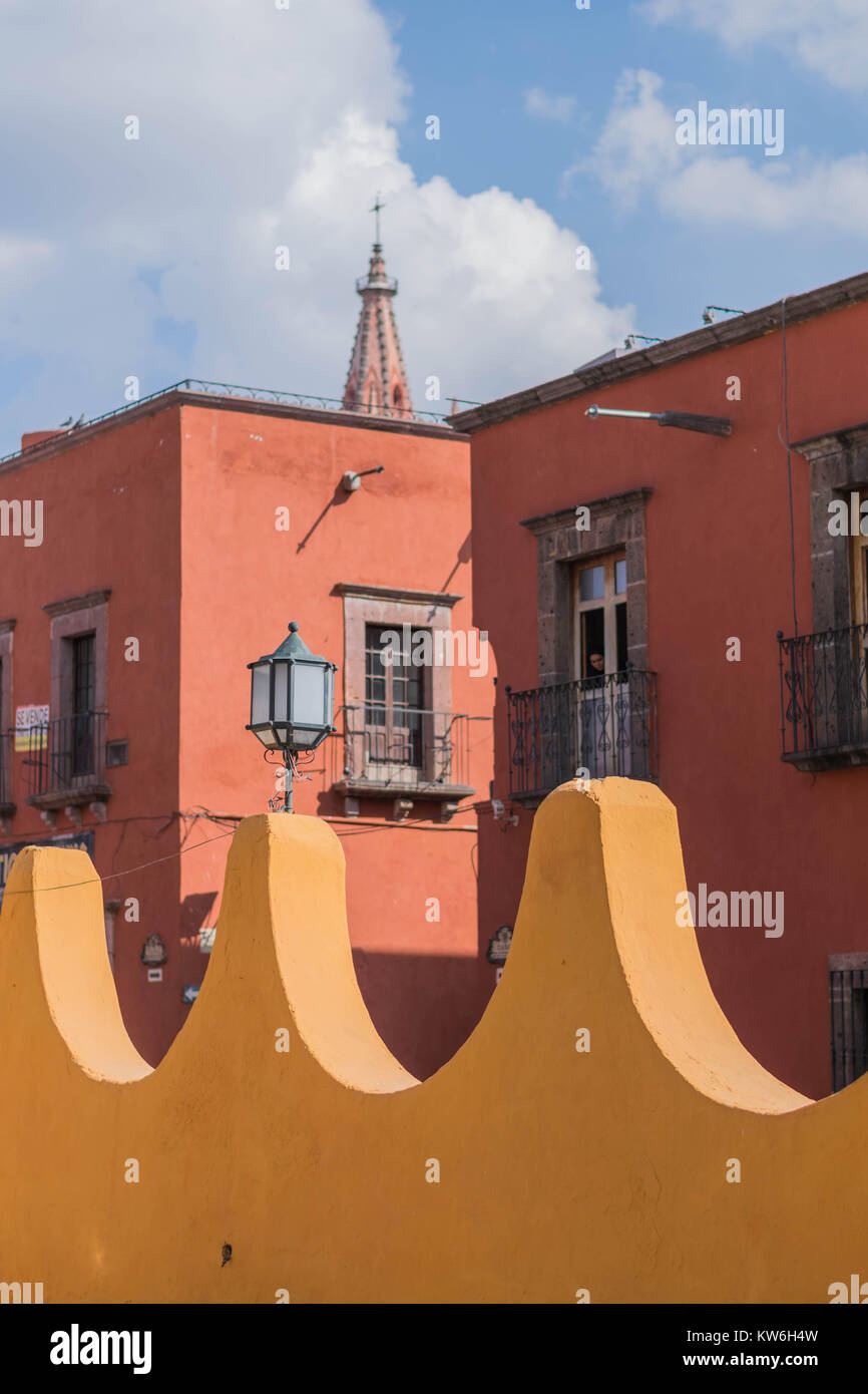 A portion of the yellow outer wall of Bellas Artes, shaped like a wave, a two story old red building, the tip of Stock Photo