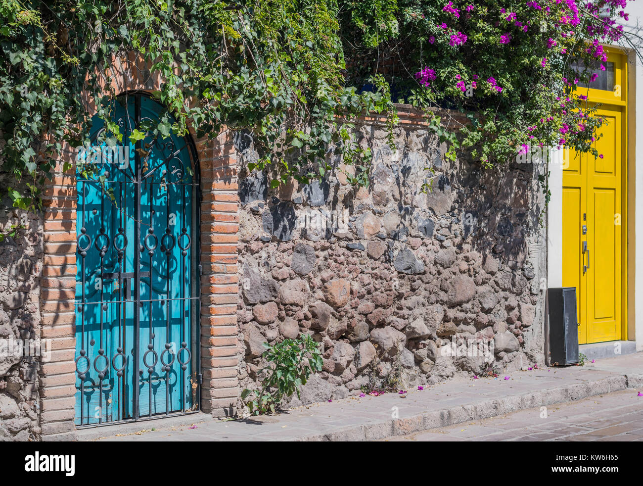 Arched blue double door with a black iron gate, a stone wall and a yellow double door, a stone walkway and some - Stock Image