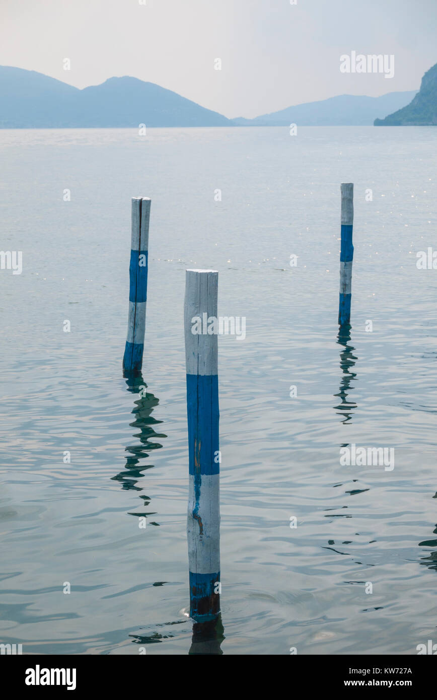 Striped mooring poles at a dock at Lake Iseo in Italy - Stock Image