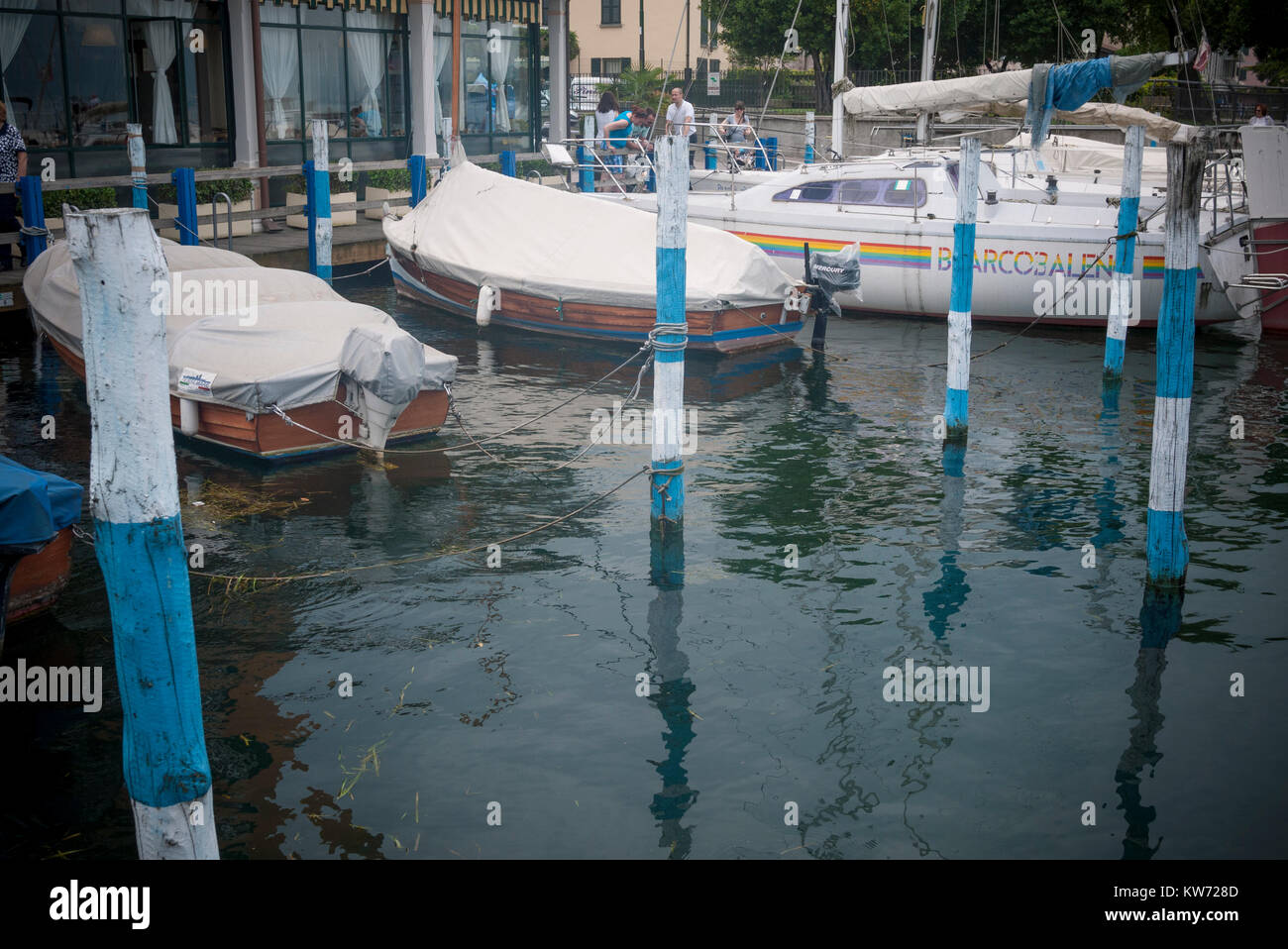 Boats moored on the jetty by Lake Iseo, Italy Stock Photo