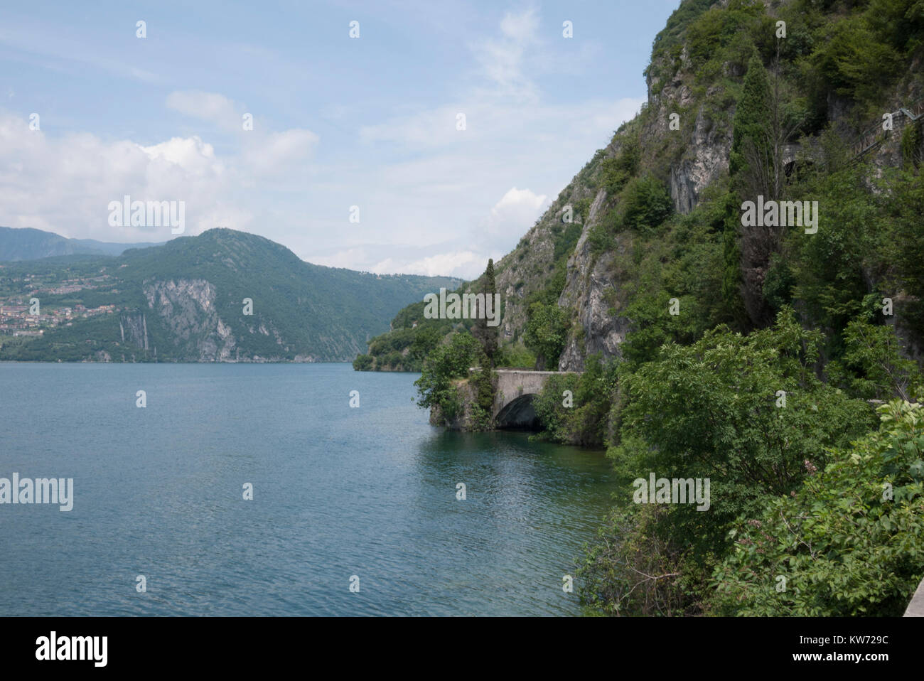 Looking across Lake Iseo from the bike trail that runs alongside it. - Stock Image