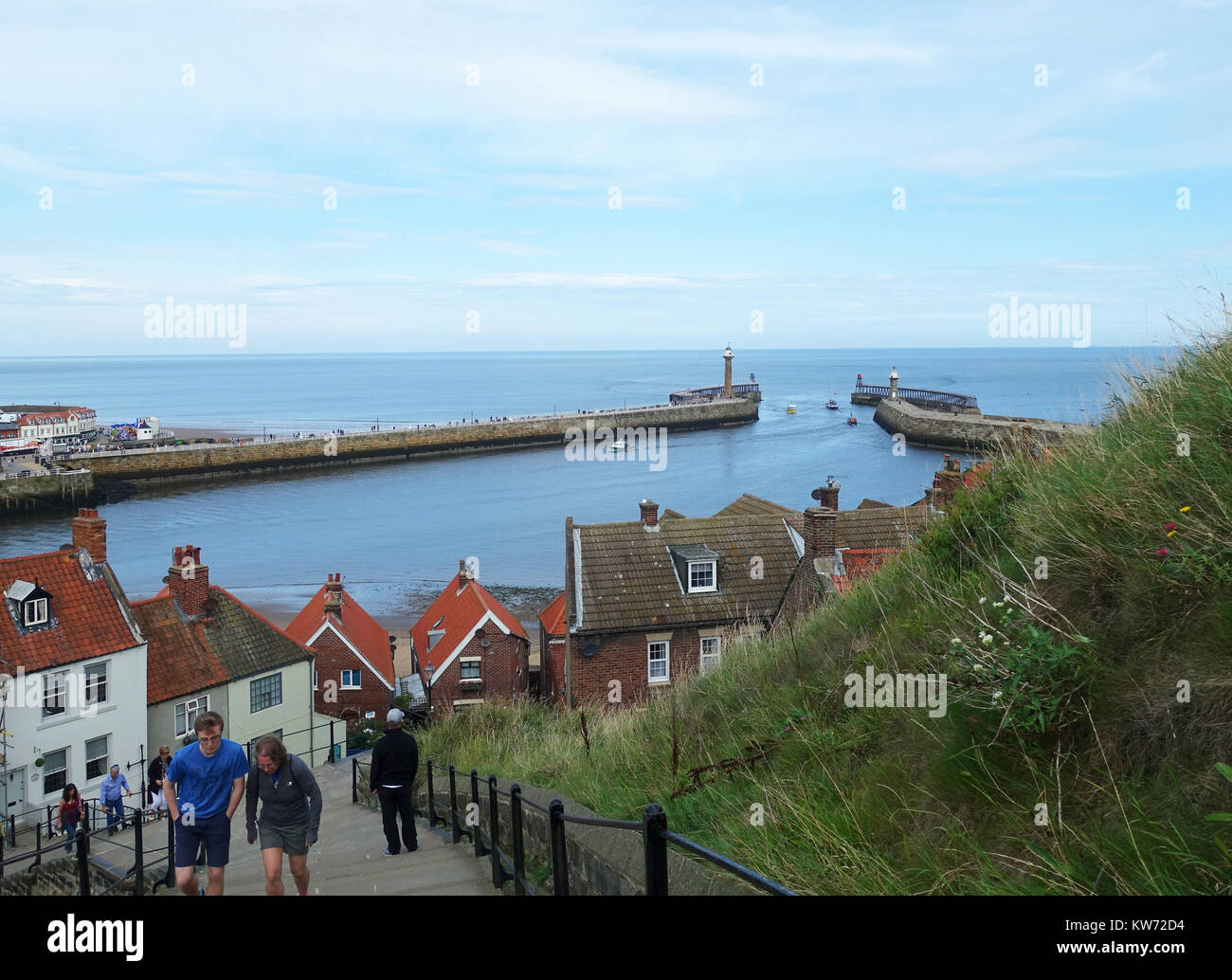 People climbing the 199 steps to Abbey and church against backdrop of Whitby Harbour. - Stock Image