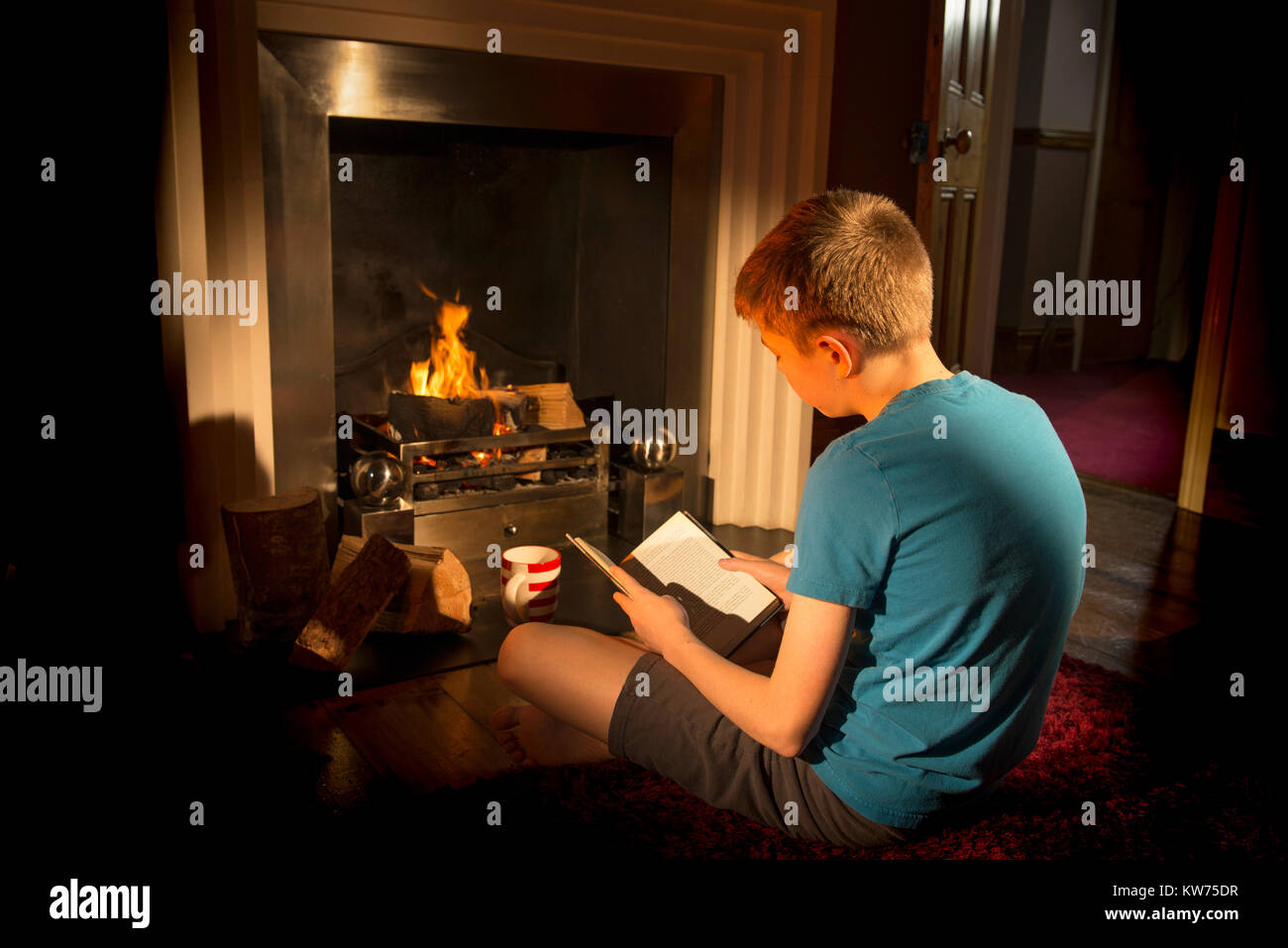 Teenage boy reading beside the fire. Hygge - Stock Image