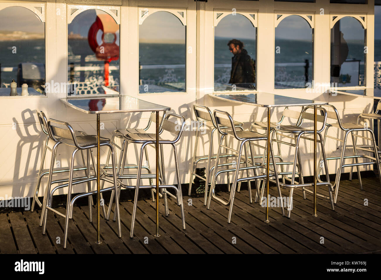 Aluminium tables and chairs wait for diners at an outdoor cafe on Brighton Pier - Stock Image