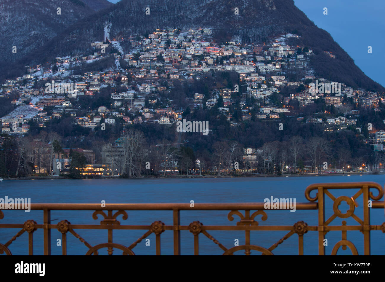 the mountain on Lake Lugano, dotted with lights in the evening Stock Photo