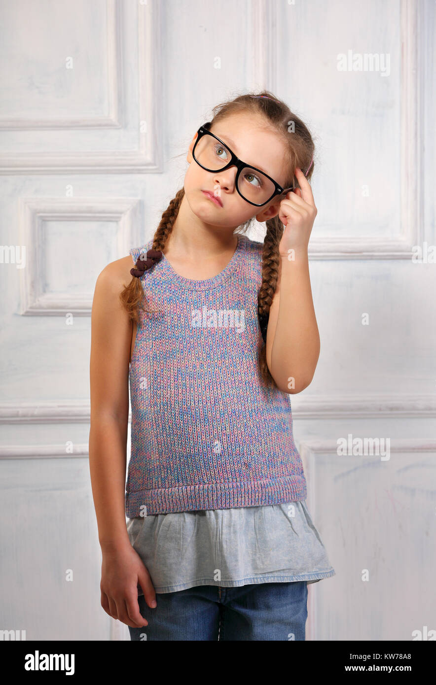 a7312c5d74 Happy thinking kid girl in fashion glasses and blouse with serious  emotional face scratching the head on blue studio background