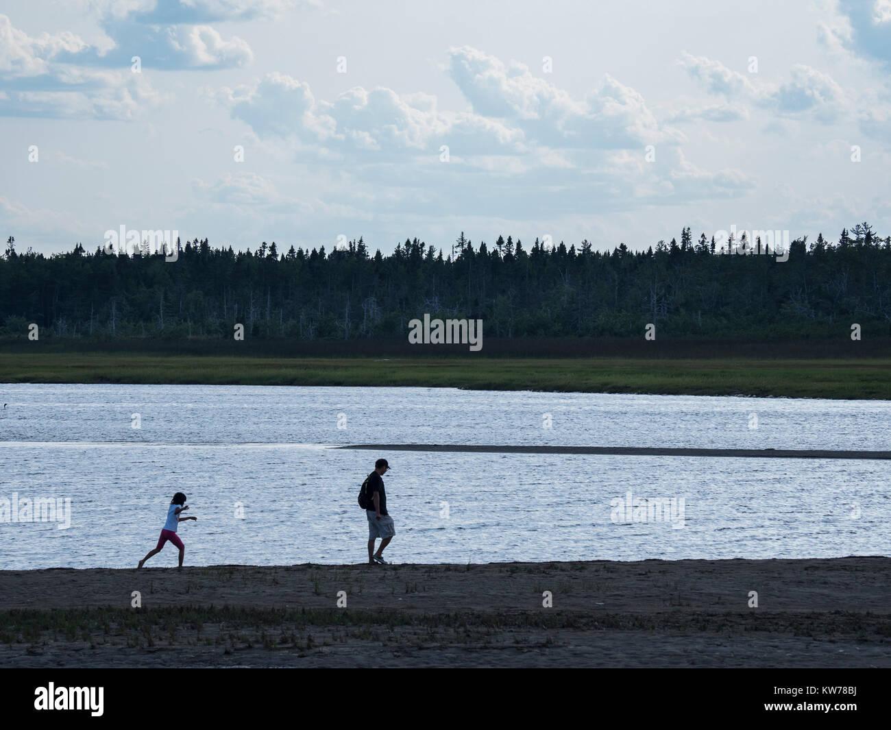 Family walks at the edge of the lagoon behind South Kouchibouguac Dune, Kouchibouguac National Park, New Brunswick, - Stock Image