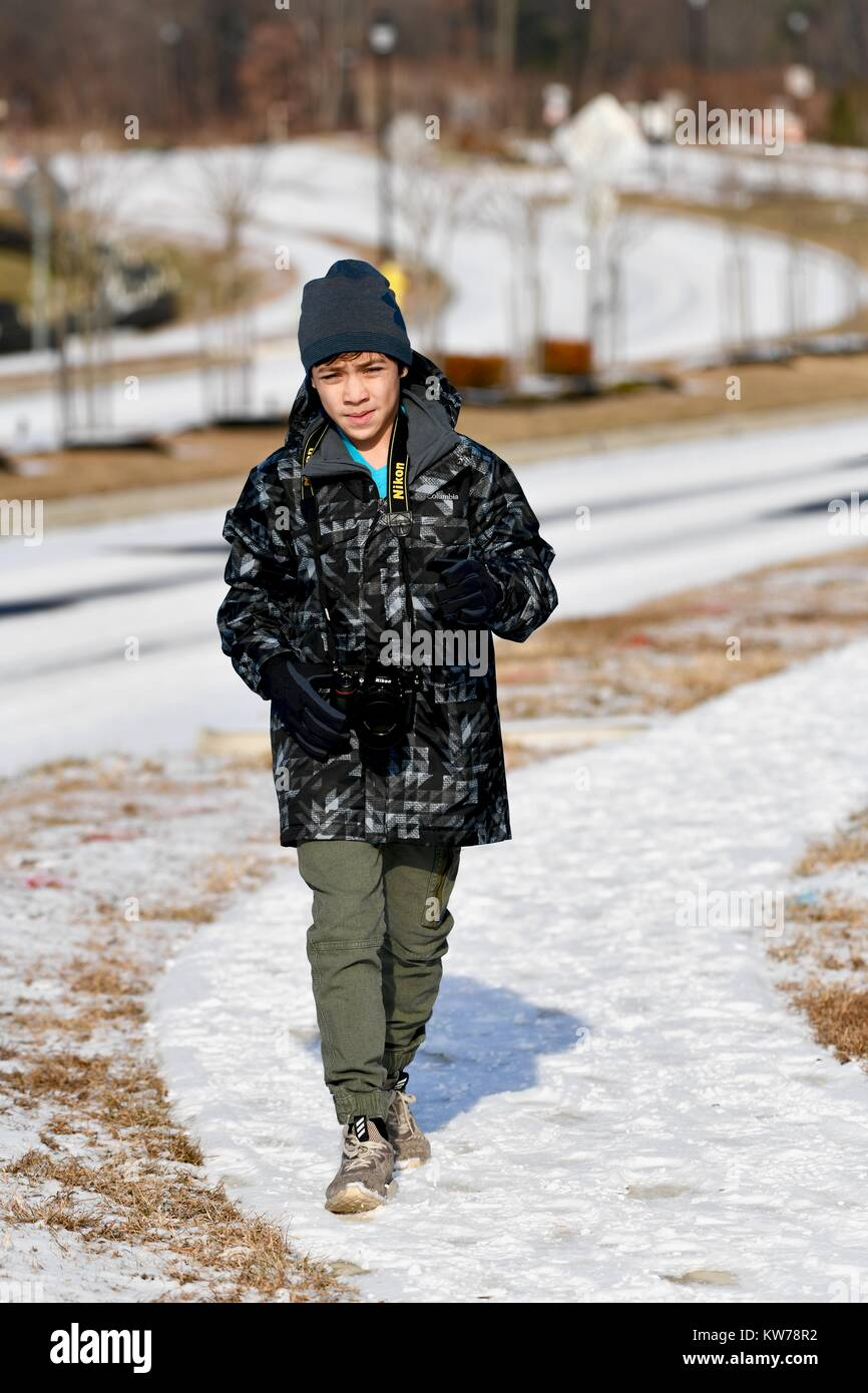 Young teenage male outside during winter taking photos with a Nikon DSLR camera - Stock Image