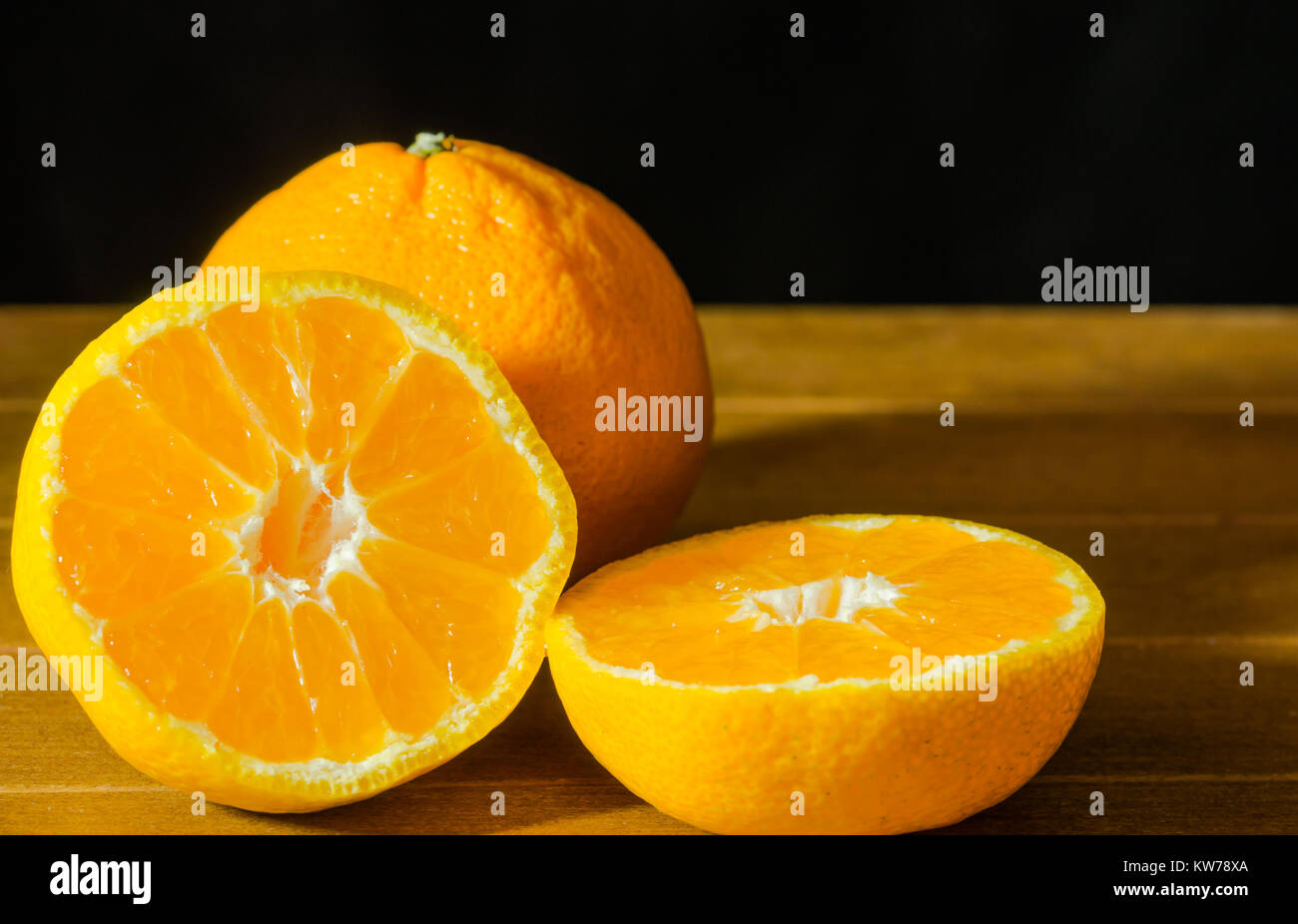 Ripe Mandarin fruit peeled open and place on old rustic look timber with group of mandarin fruits out of focus on - Stock Image