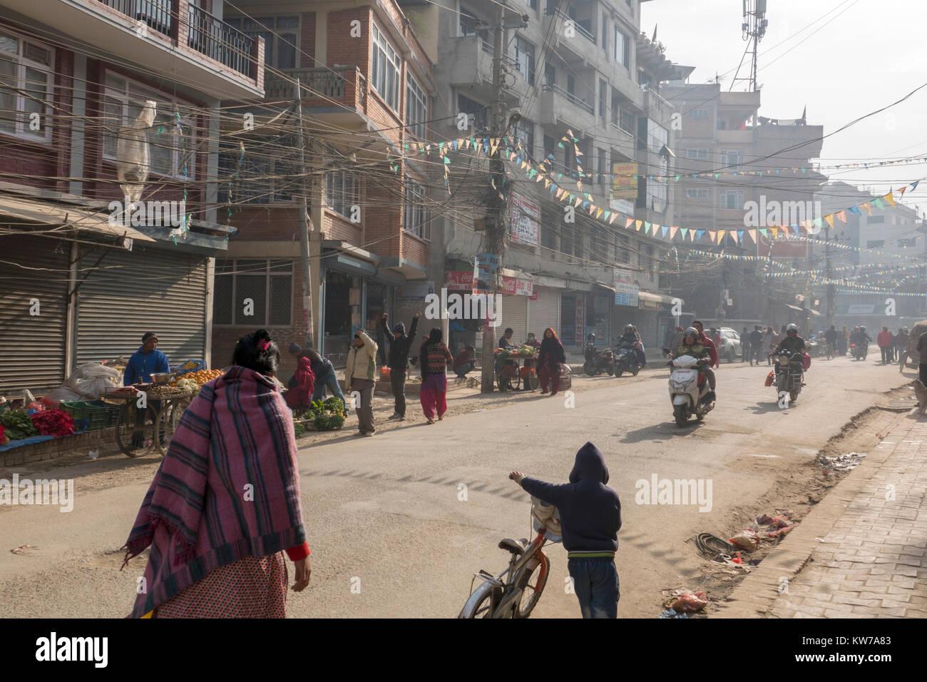People in cold dusty streets of wintertime Kathmandu, Nepal - Stock Image