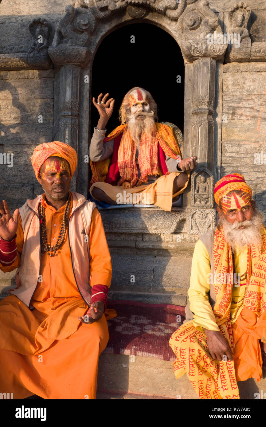 Sadhu holy men sitting for photos at Pashupatinath temple in Kathmandu. Having denounced the material world they - Stock Image