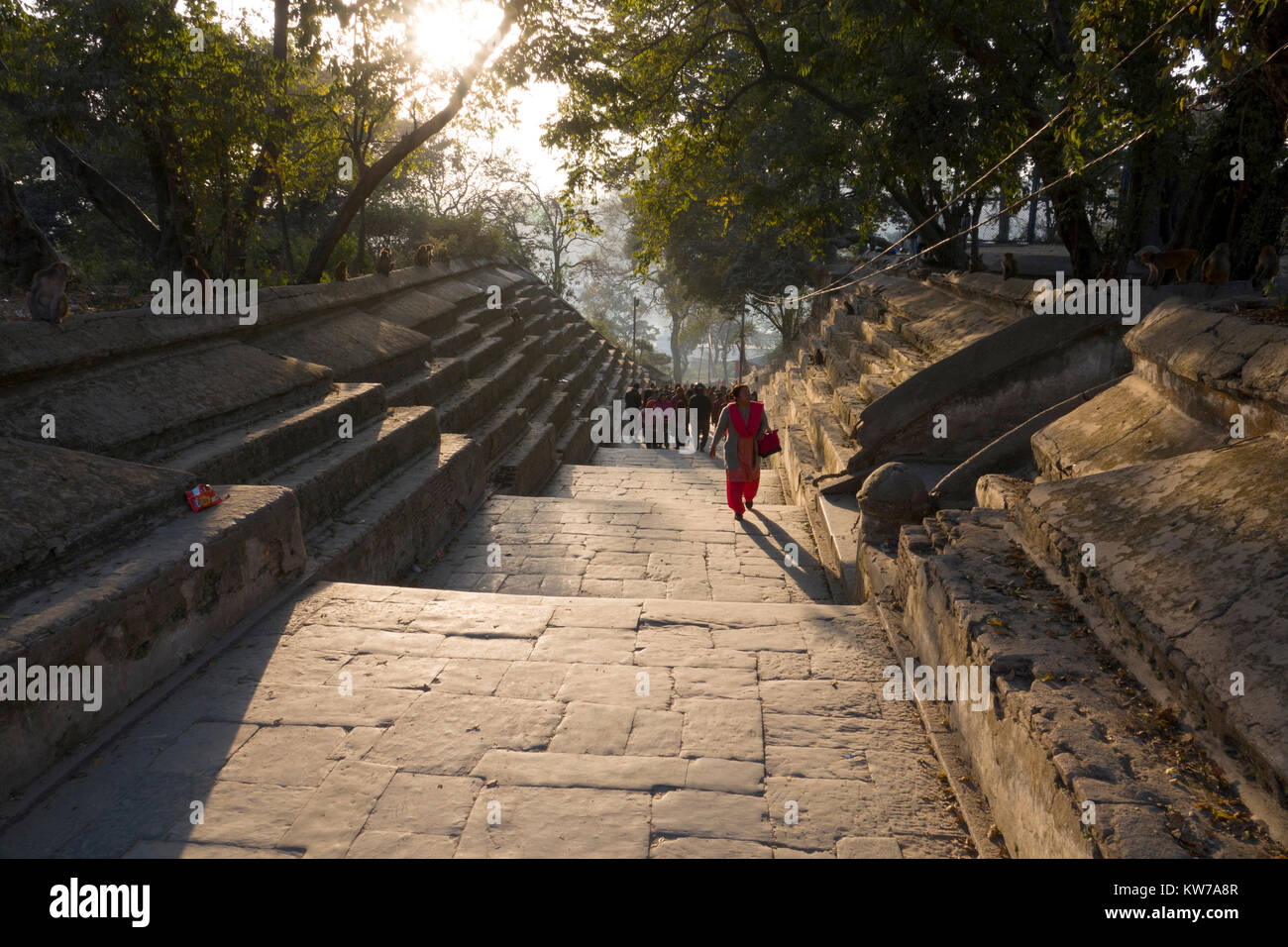 People walking stone steps of Pashupatinath Temple in Kathmadu, Nepal - Stock Image
