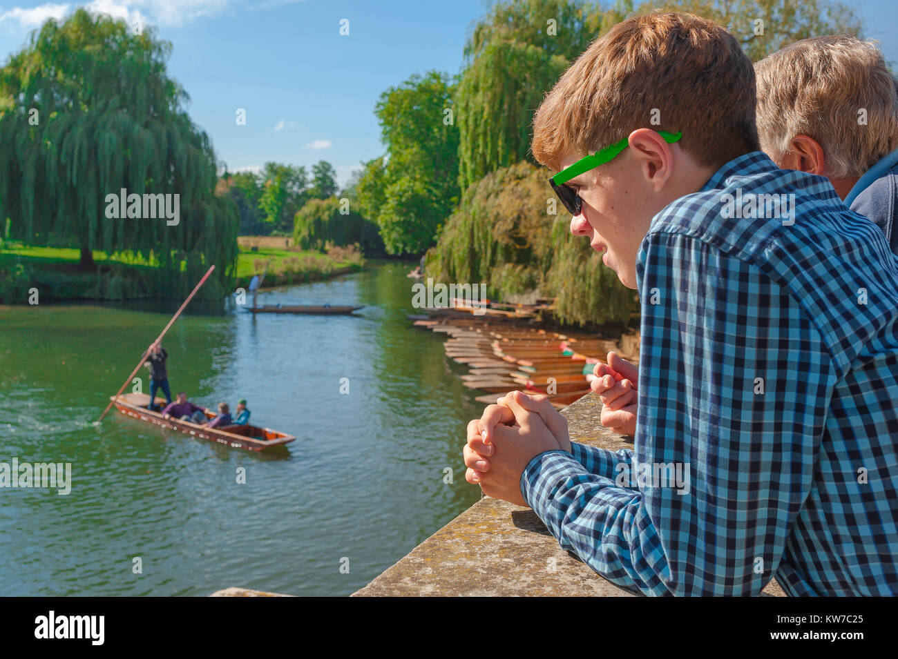Cambridge UK punting, on a summer afternoon a young tourist on Silver Street Bridge in Cambridge watches people - Stock Image
