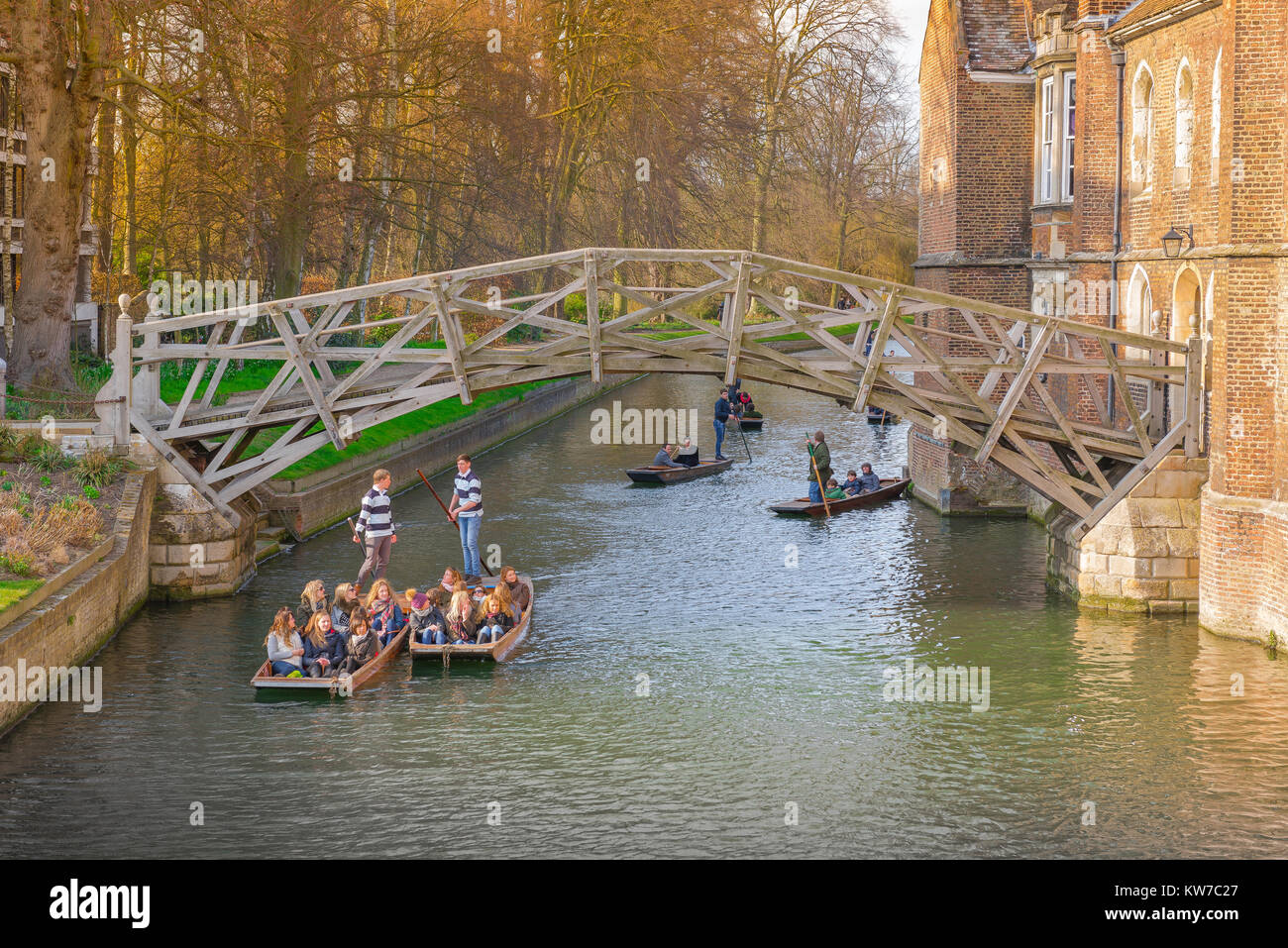 Cambridge punting, on a spring morning in Cambridge, UK, tourists ride in punts on the River Cam, gliding under - Stock Image
